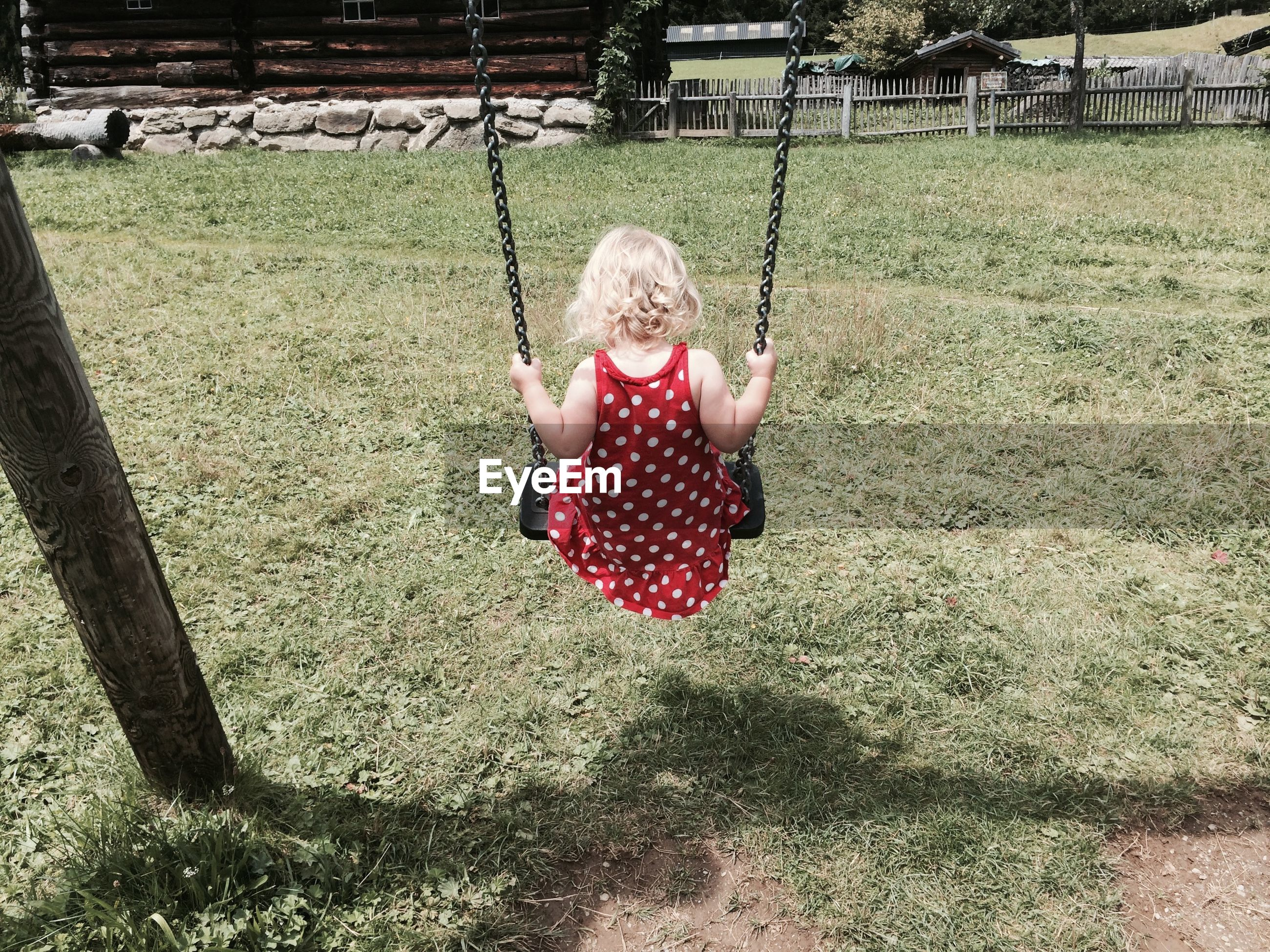 Rear view of girl on swing at field