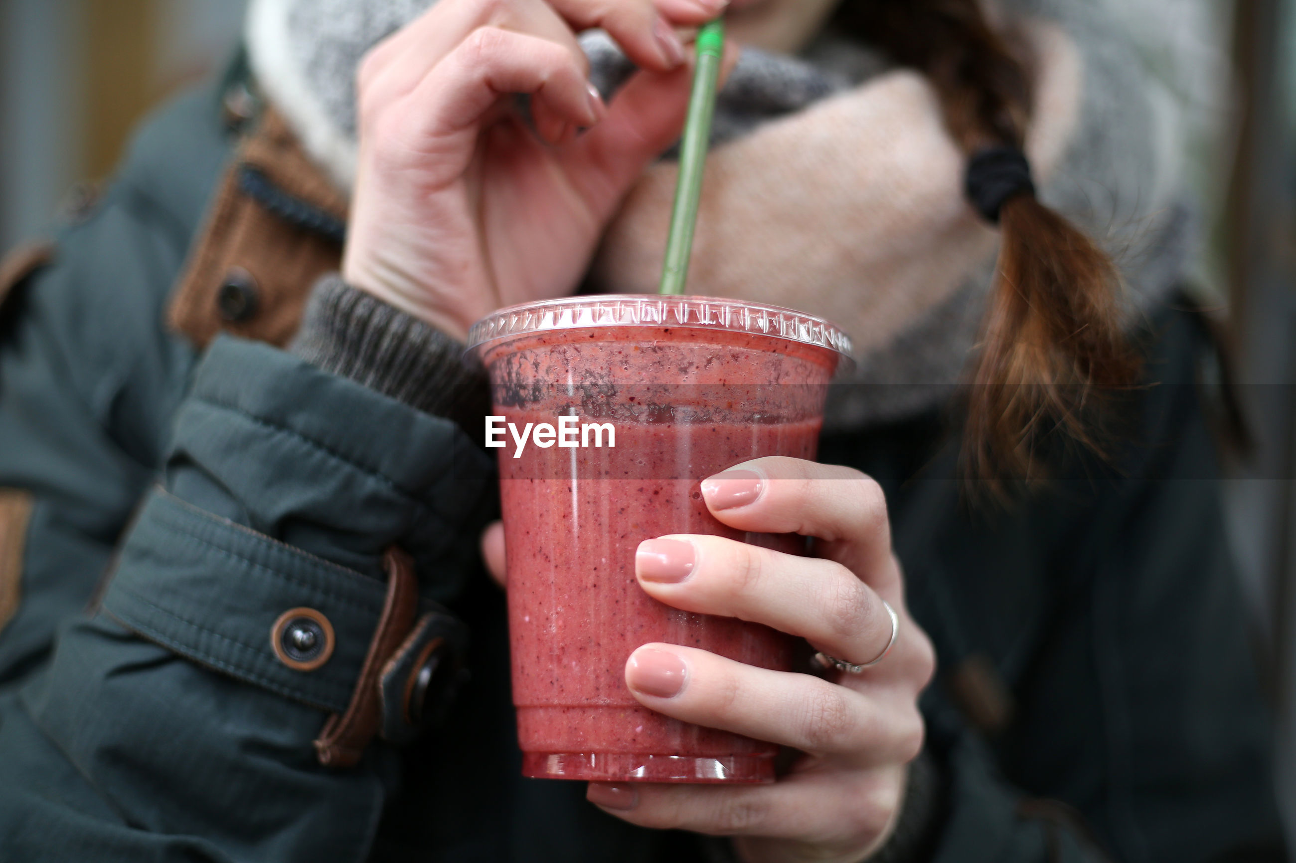 Midsection of woman having smoothie