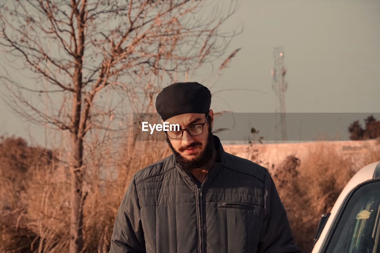 Young man wearing eyeglasses standing outdoors
