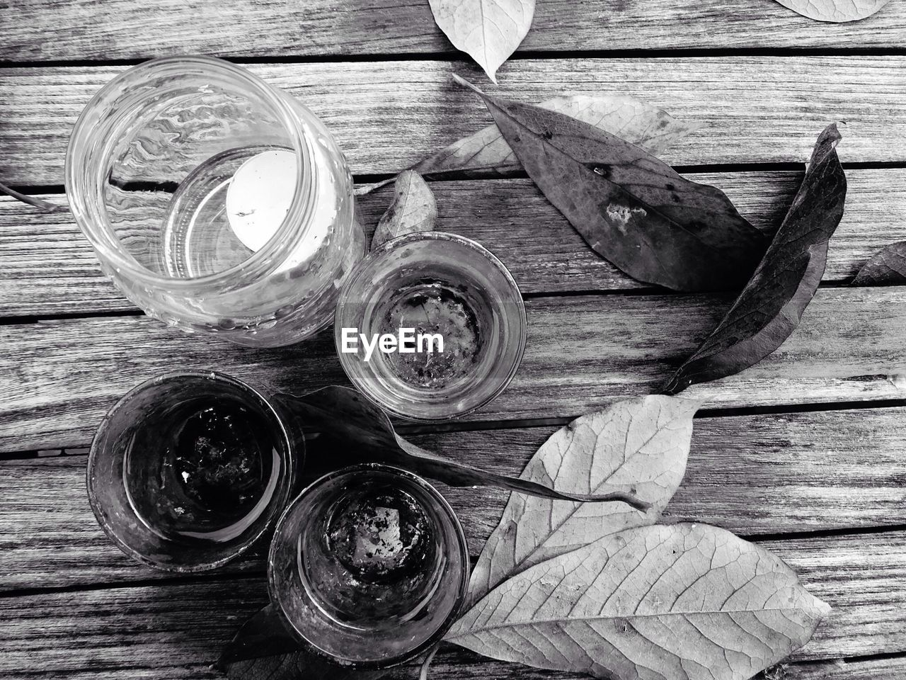 Directly Above Shot Of Glasses With Jar By Autumn Leaves On Table