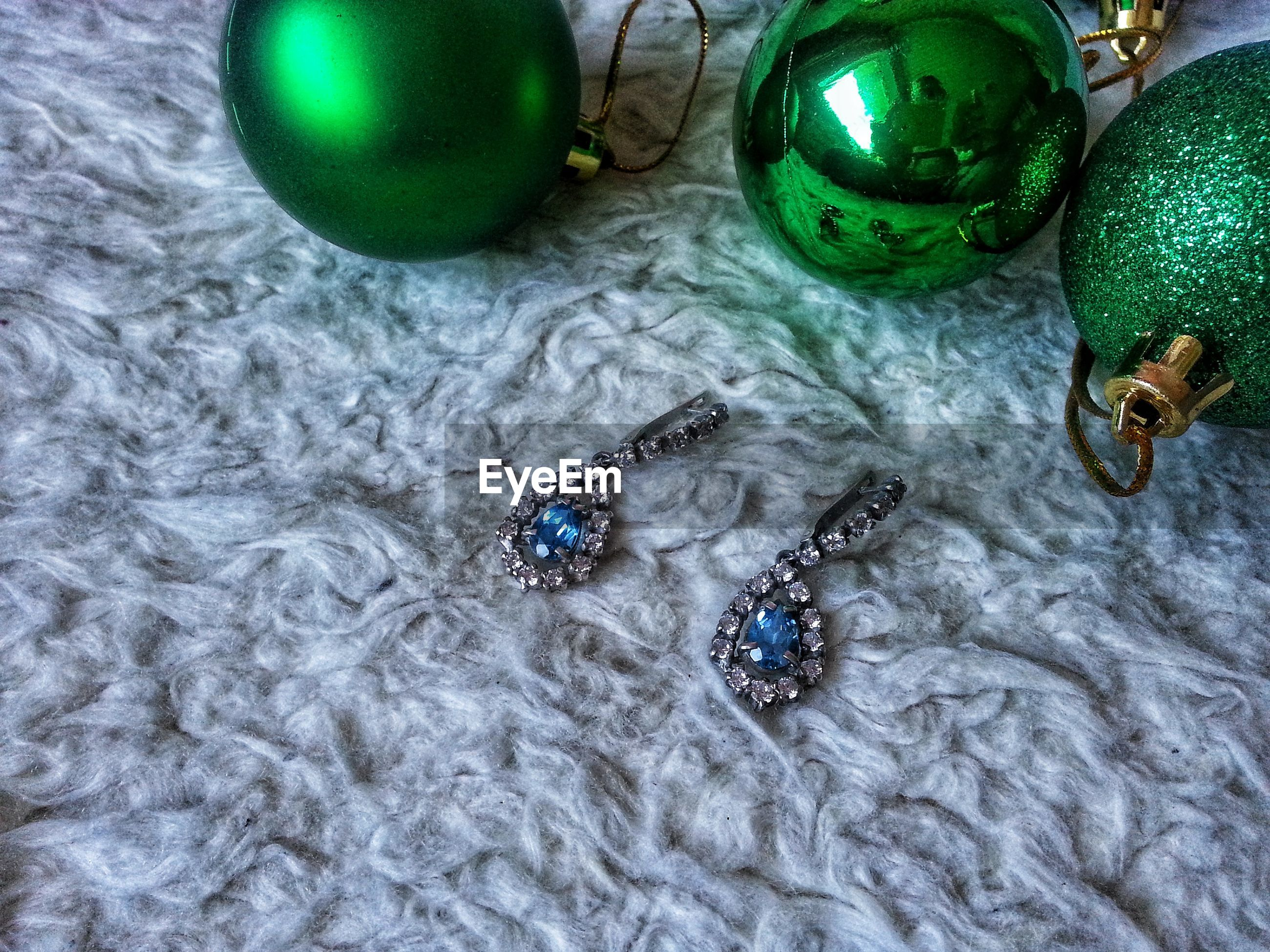 High angle view of earrings with christmas ornaments on cotton