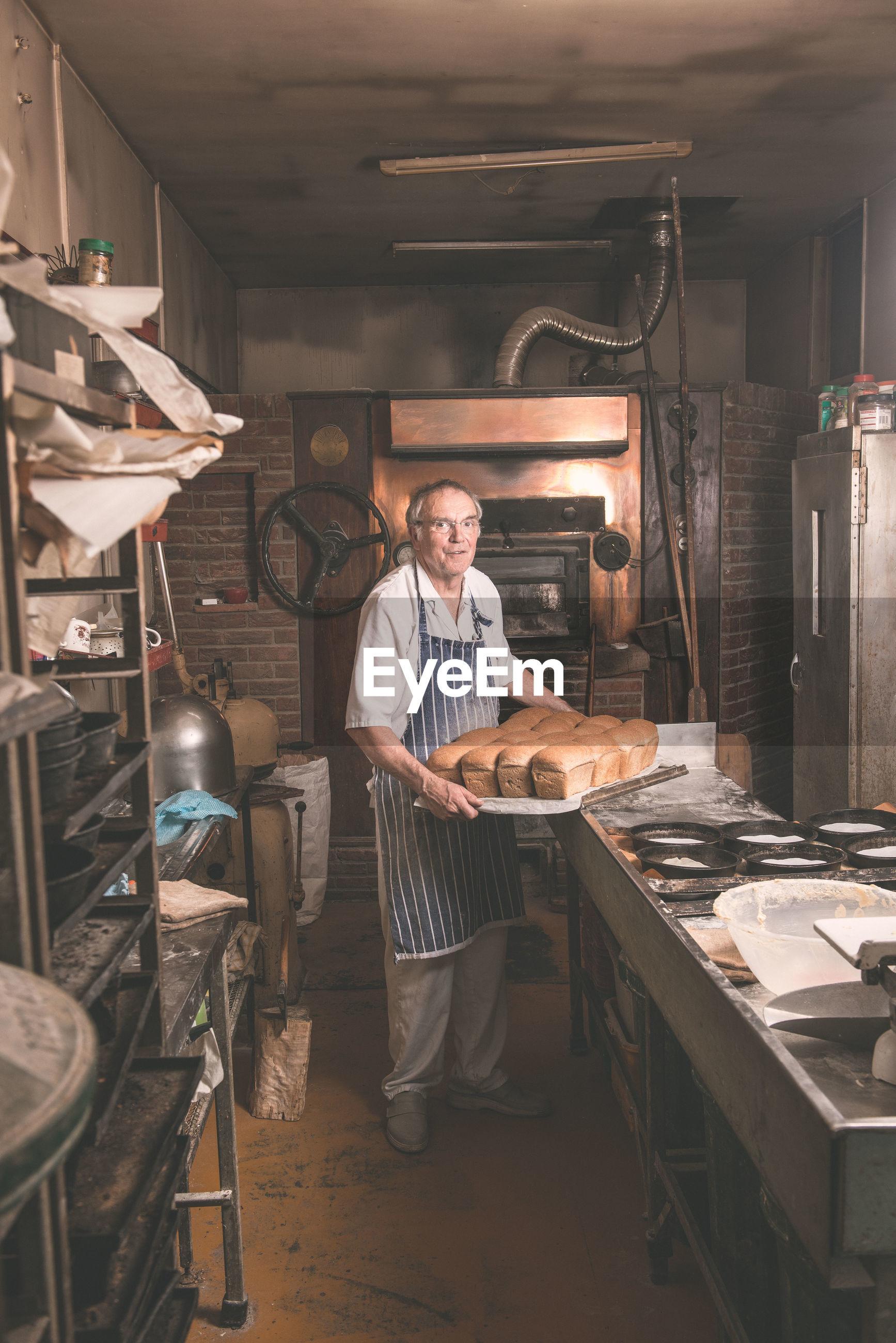 Full length portrait of baker holding breads in tray at bakery