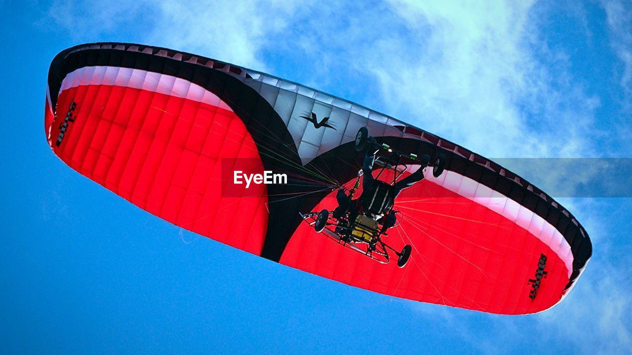 low angle view, sky, red, blue, outdoors, day, arts culture and entertainment, leisure activity, adventure, parachute, extreme sports, real people, paragliding