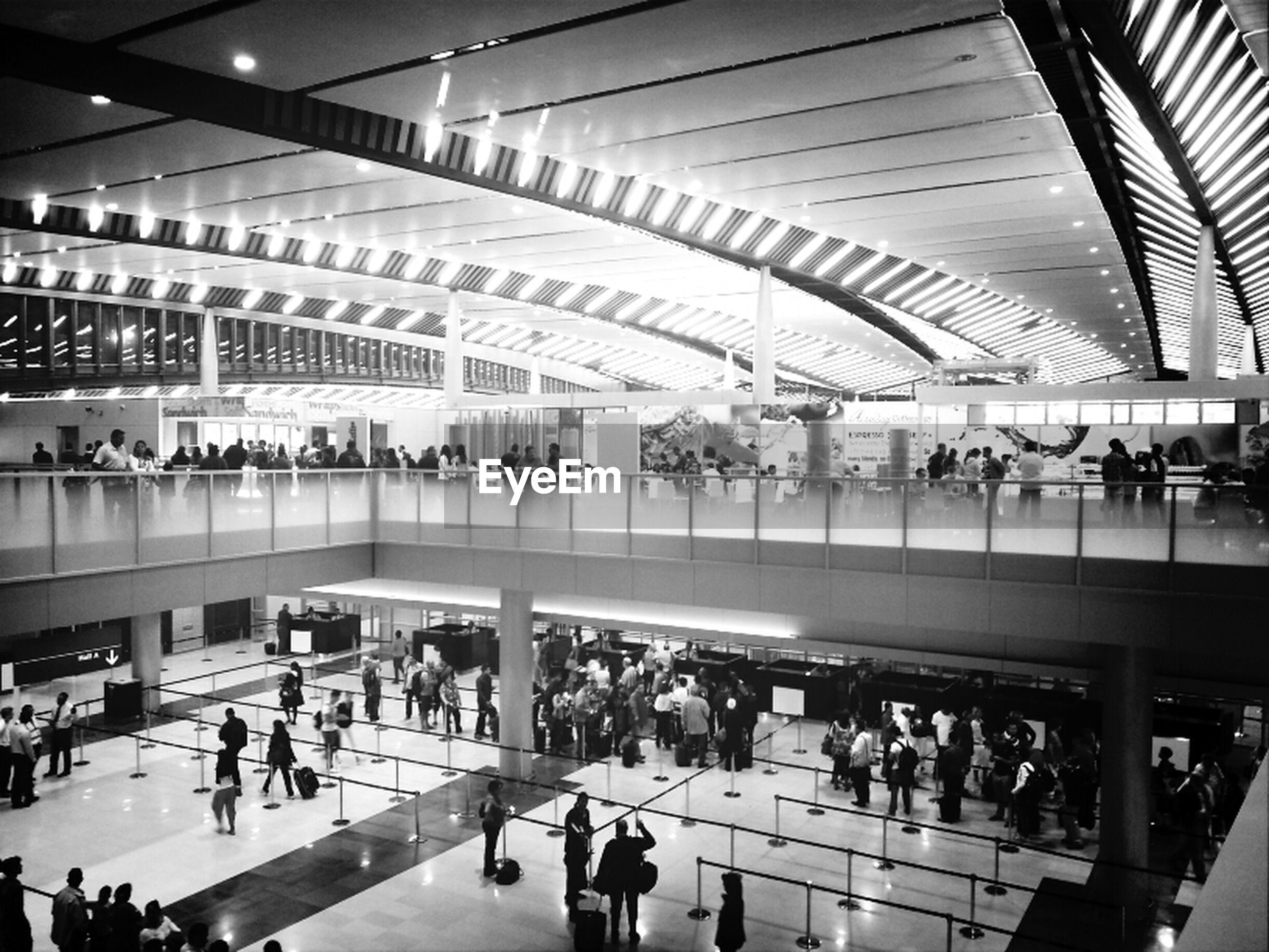 large group of people, indoors, railroad station, public transportation, person, railroad station platform, men, architecture, built structure, transportation, rail transportation, lifestyles, city life, walking, transportation building - type of building, passenger, modern, shopping mall, ceiling