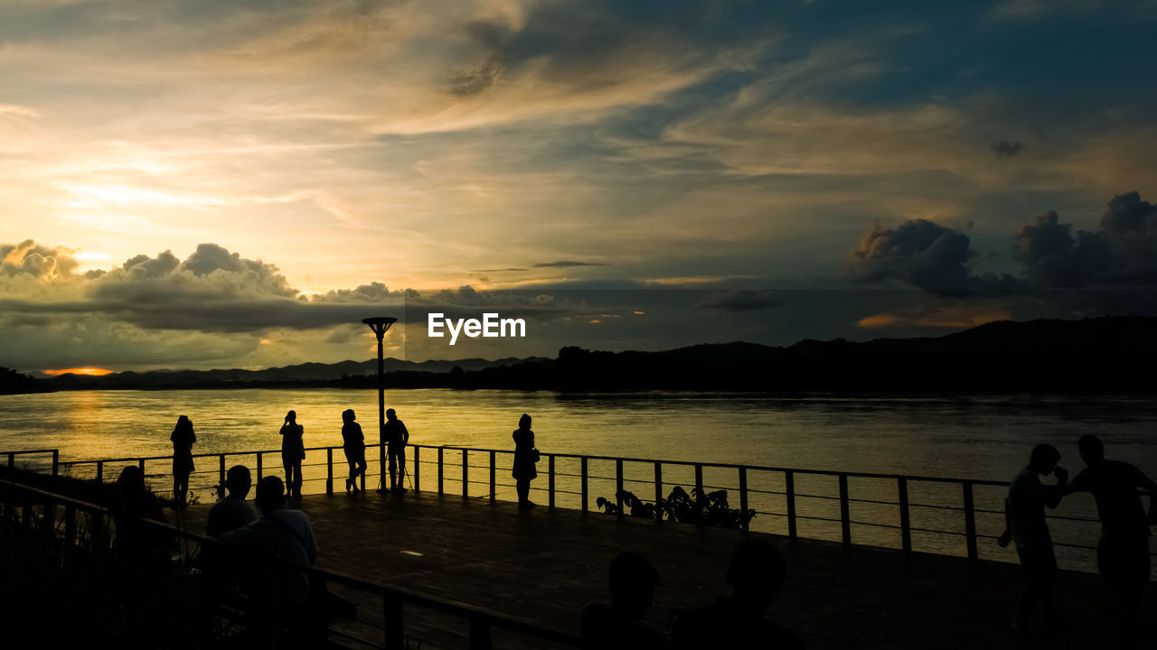 cloud - sky, water, sky, sunset, beauty in nature, scenics - nature, group of people, railing, real people, sea, nature, men, silhouette, orange color, lifestyles, outdoors, women, transportation, idyllic
