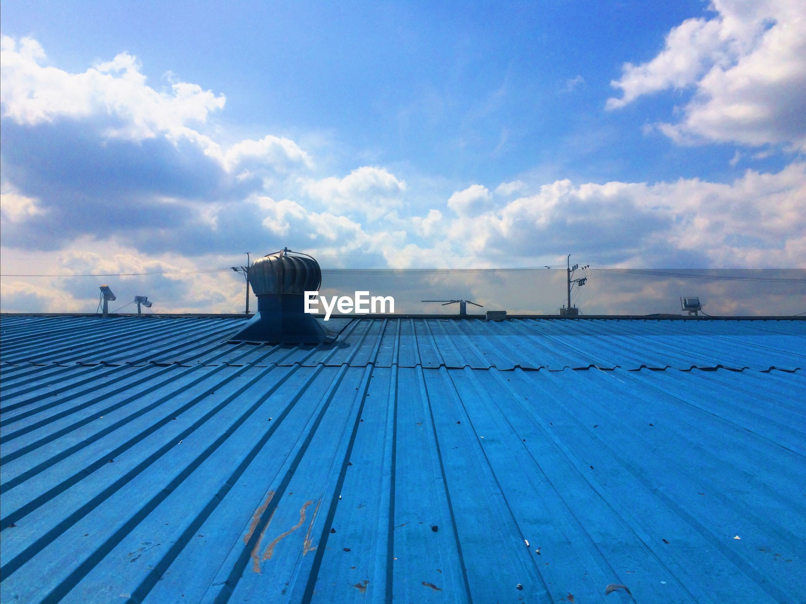 Low angle view of ventilator on blue industry roof against sky