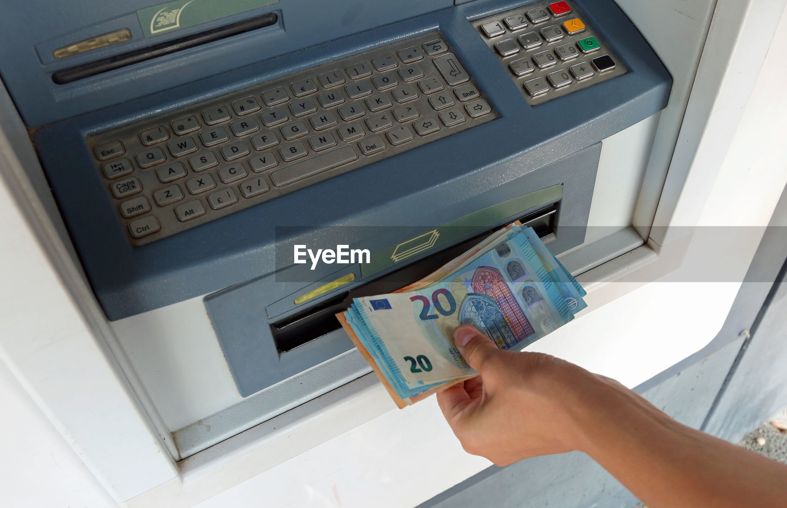 Cropped hand withdrawing paper currency from atm