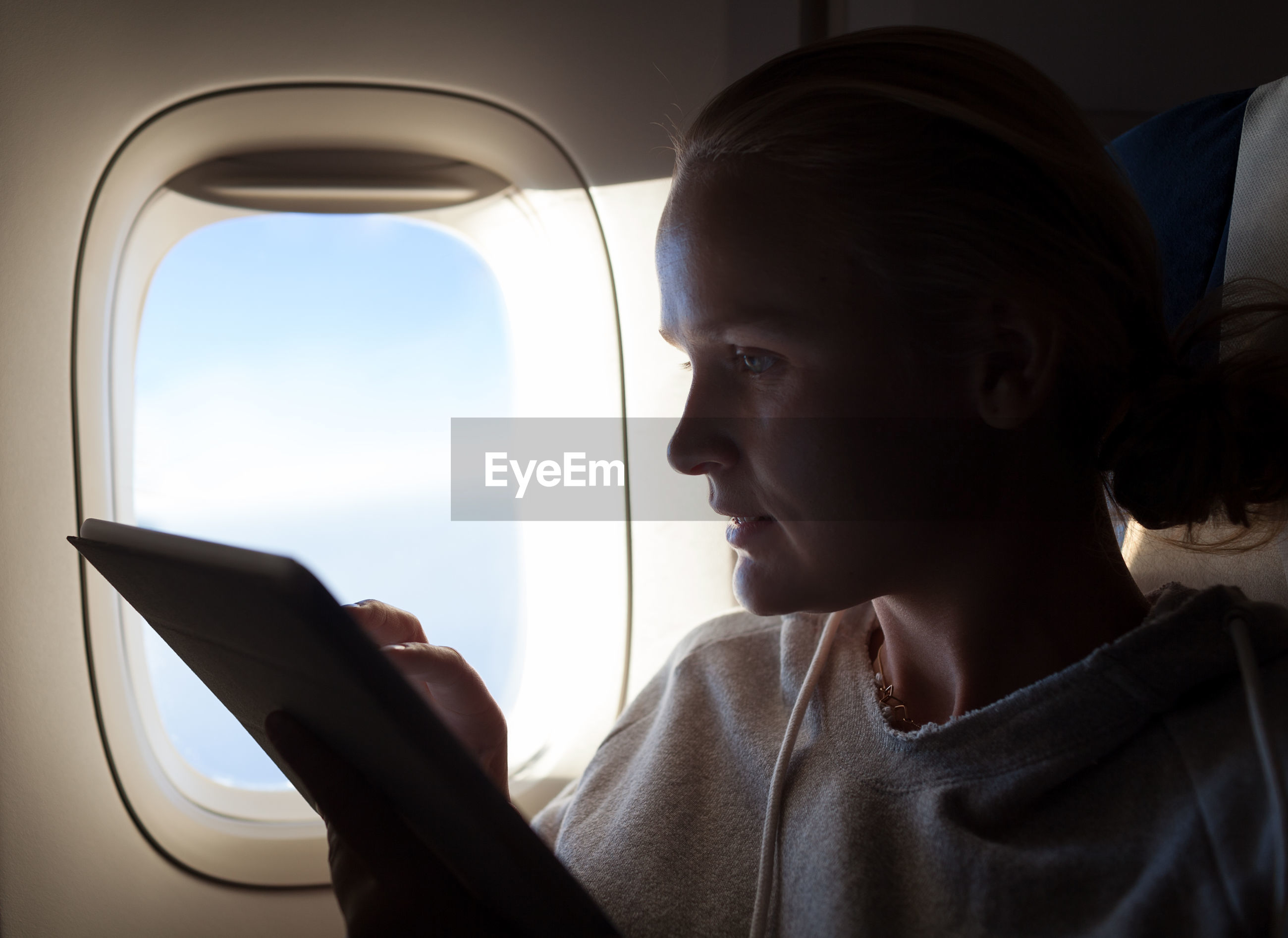 Woman using digital tablet while sitting in airplane