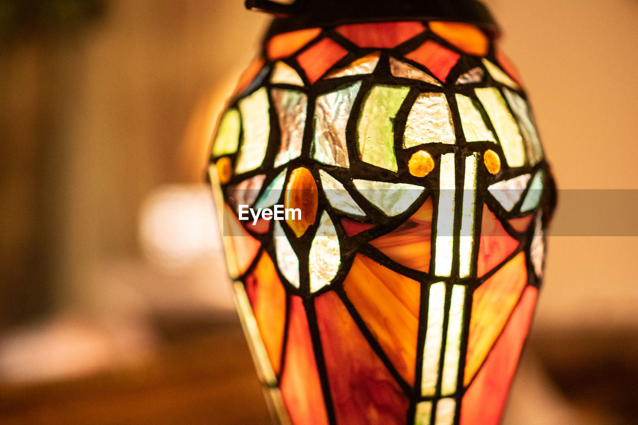 focus on foreground, close-up, art and craft, creativity, no people, pattern, indoors, lighting equipment, multi colored, decoration, orange color, representation, design, craft, illuminated, single object, glass - material, human representation, electric lamp, still life, floral pattern