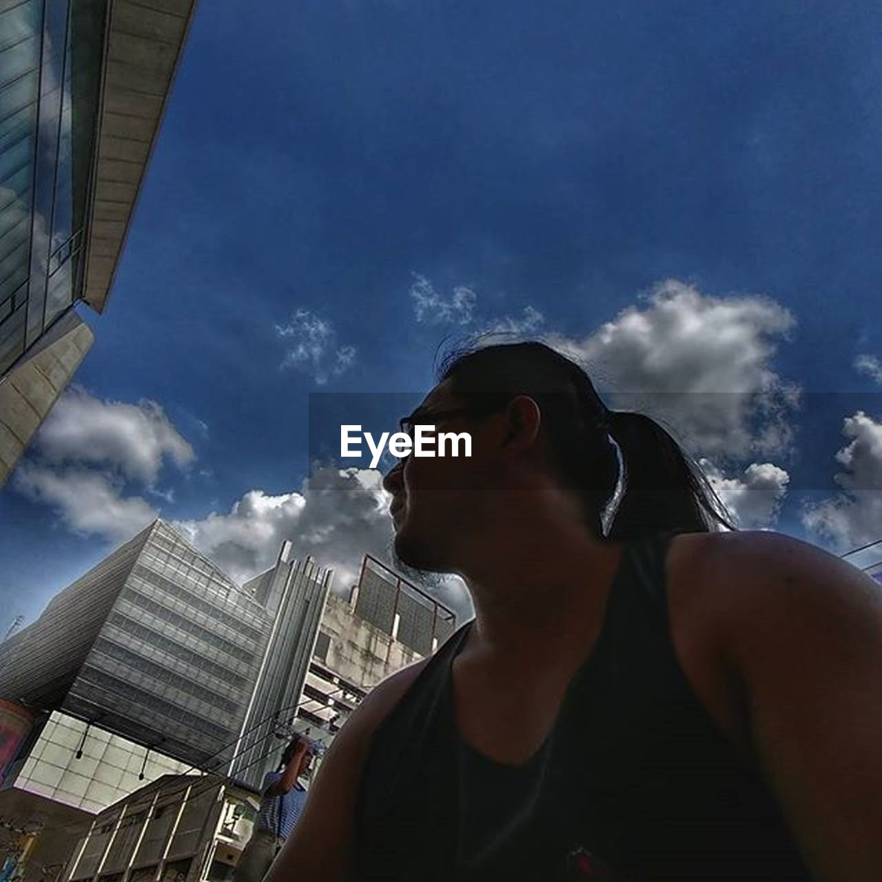 skyscraper, building exterior, architecture, sky, cloud - sky, city, built structure, outdoors, one person, young adult, low angle view, cityscape, headshot, real people, day, urban skyline, young women, adult, people, adults only