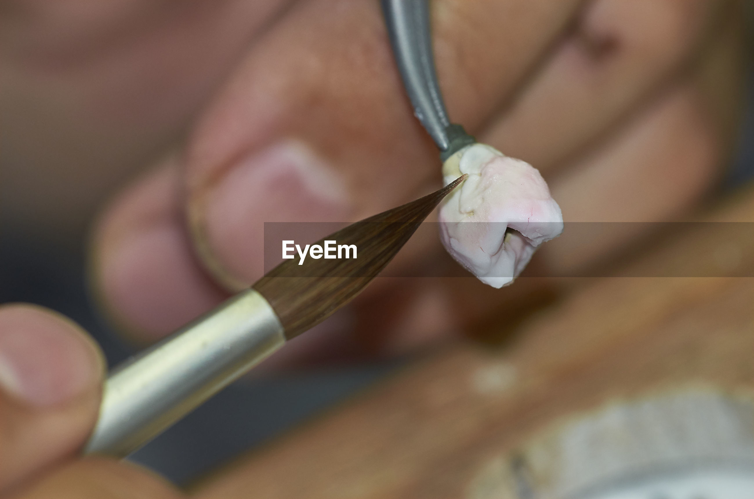 Close-up of hand using paintbrush on tooth