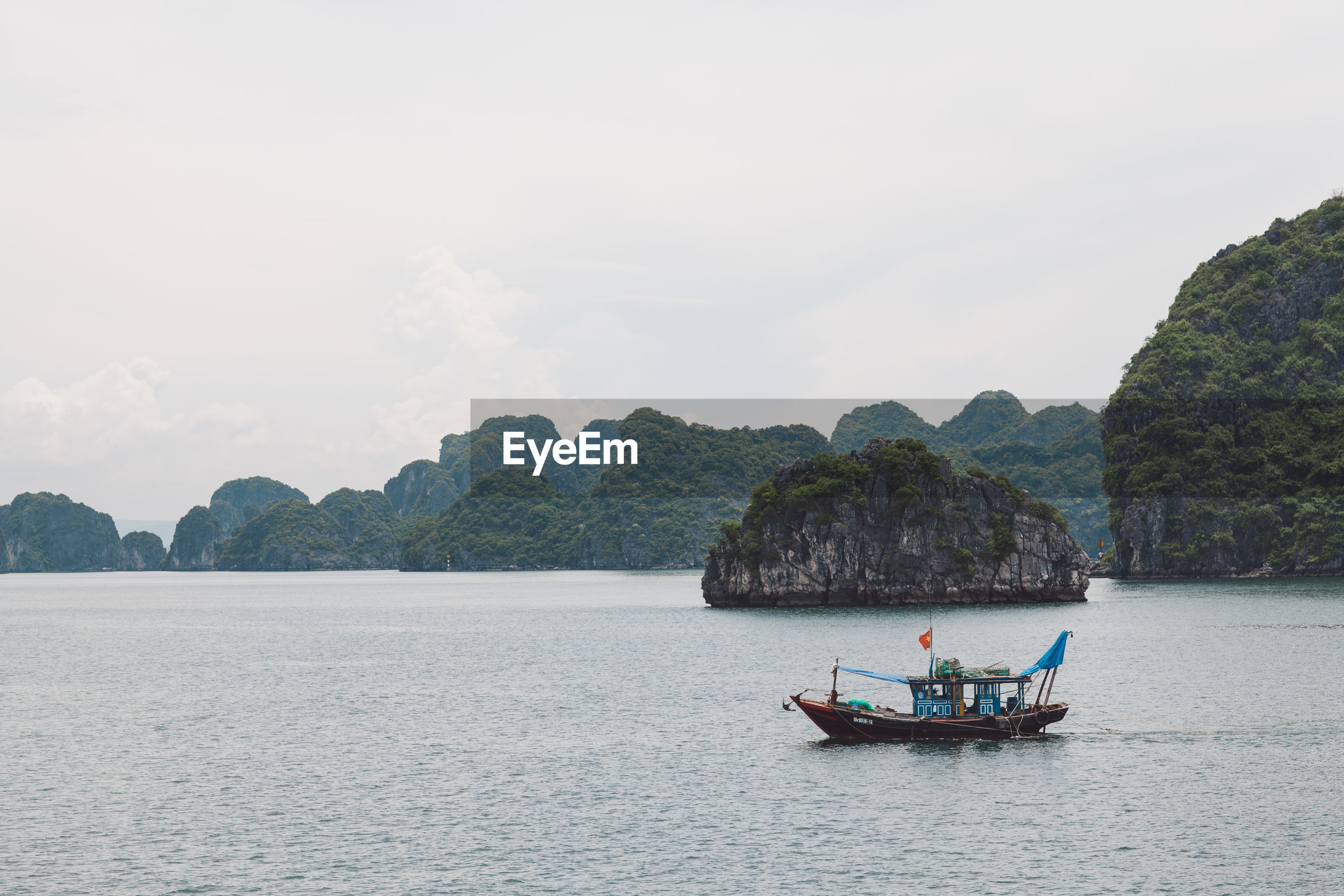 Fishing boat on halong bay by mountain