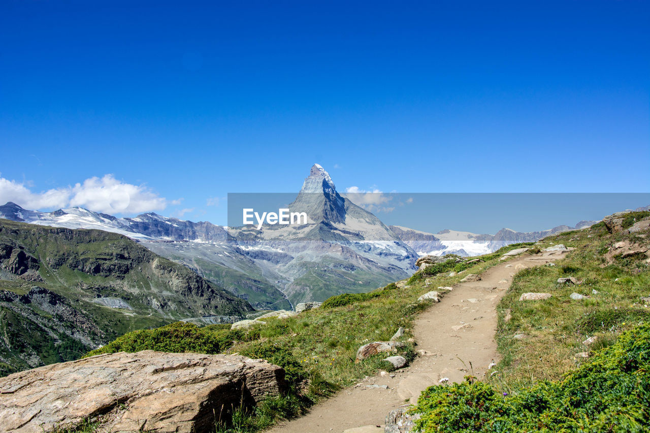 mountain, sky, beauty in nature, scenics - nature, landscape, tranquil scene, blue, environment, nature, tranquility, mountain range, non-urban scene, no people, day, clear sky, road, idyllic, plant, copy space, snow, outdoors, mountain peak, snowcapped mountain