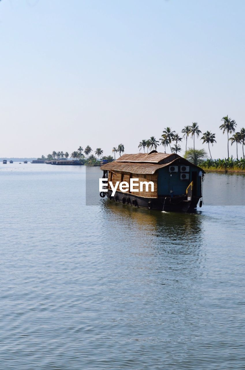 Boat House In Lake Against Clear Sky