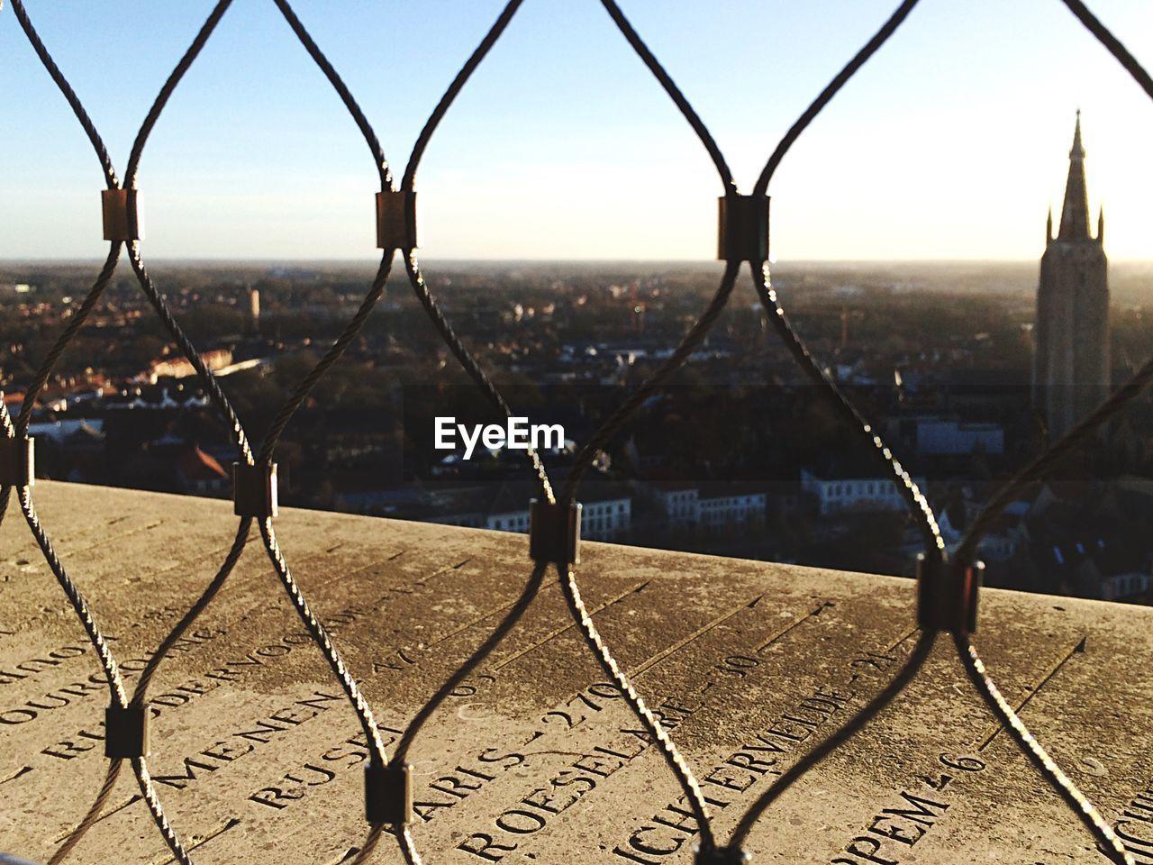City seen through metal window against clear sky