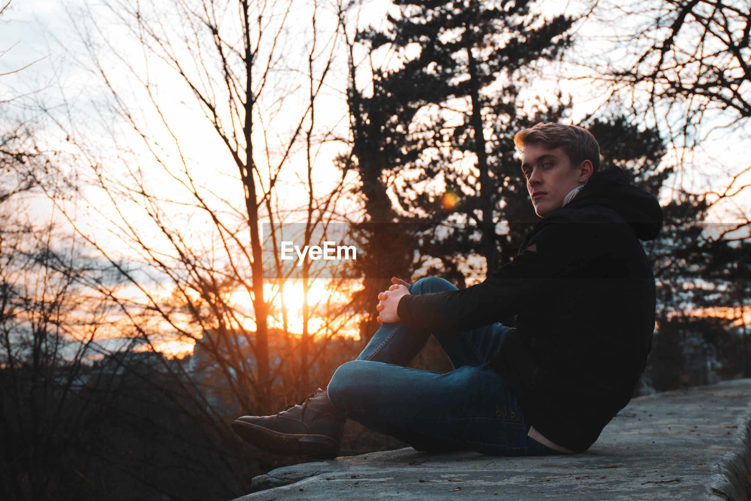 Portrait of man sitting on retaining wall against trees during sunset