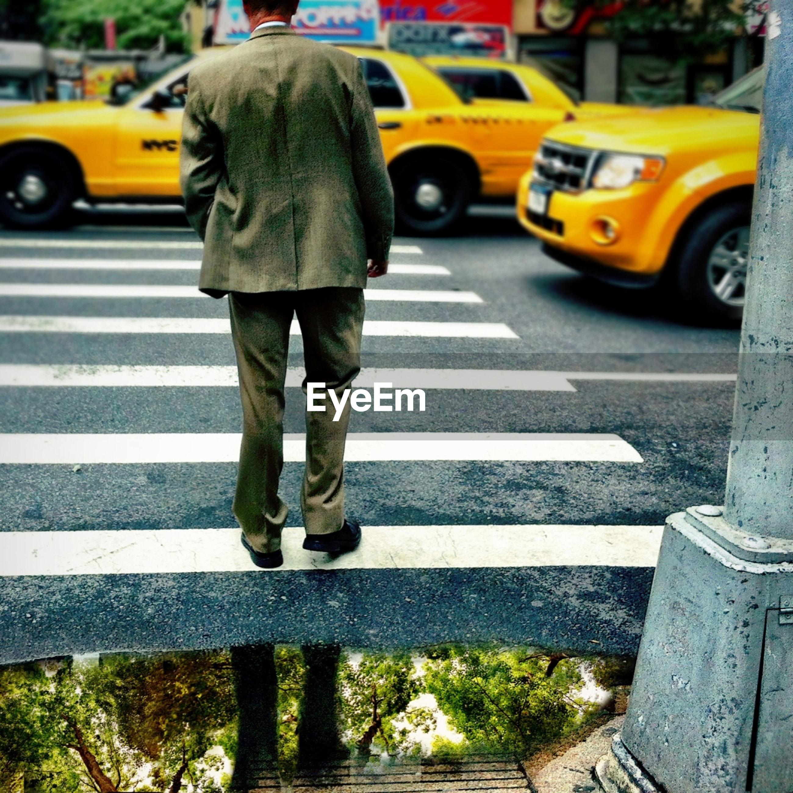 transportation, mode of transport, car, street, land vehicle, road, road marking, city, zebra crossing, on the move, rear view, city life, men, travel, walking, asphalt, day, outdoors