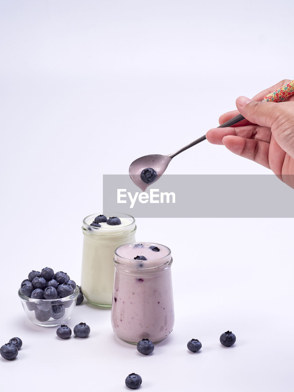 food and drink, human hand, hand, berry fruit, food, freshness, blueberry, one person, human body part, healthy eating, studio shot, fruit, indoors, white background, spoon, kitchen utensil, unrecognizable person, table, wellbeing, holding, temptation, breakfast, finger