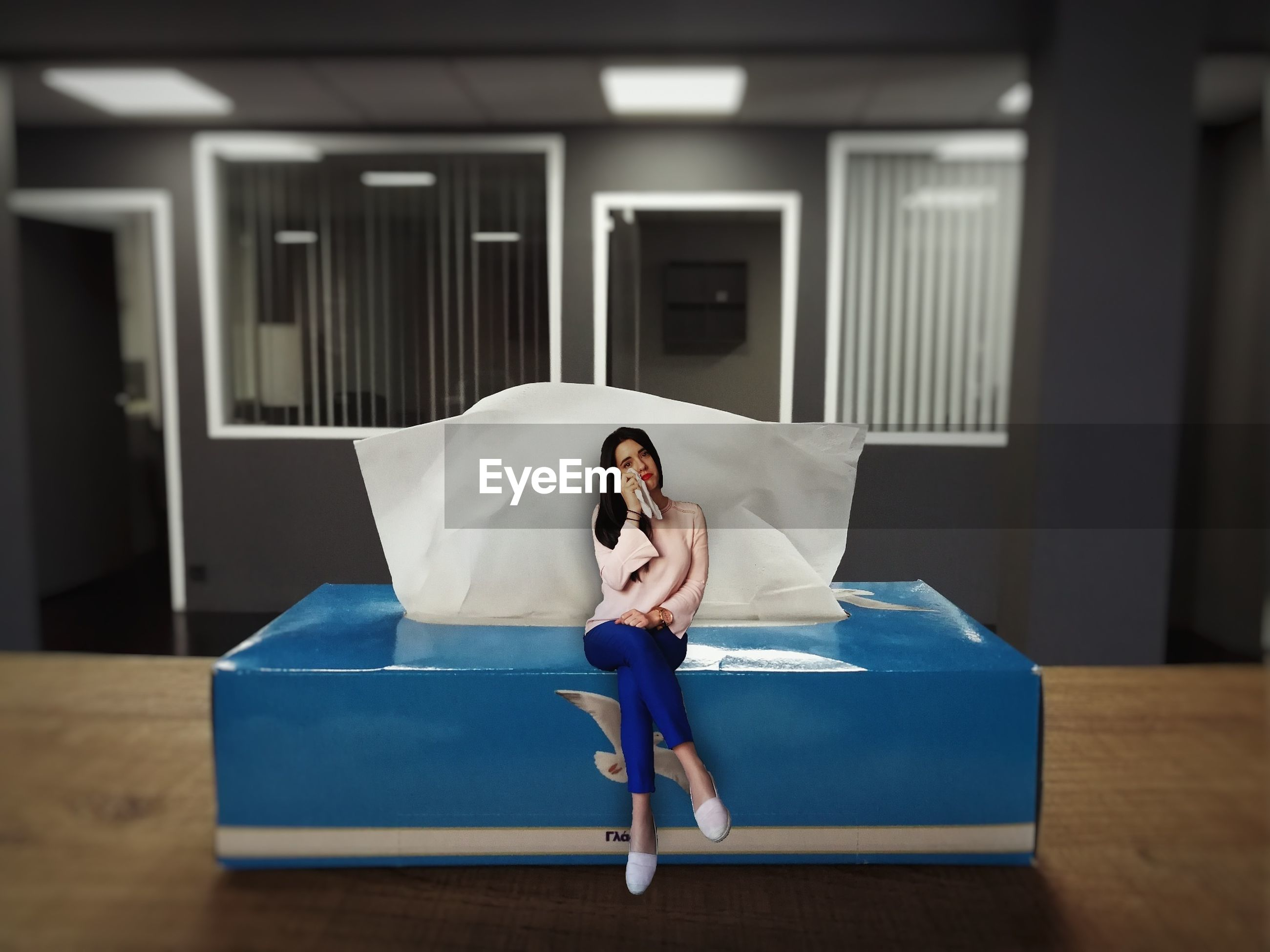Digital composite image of young woman sitting on tissue paper box at home