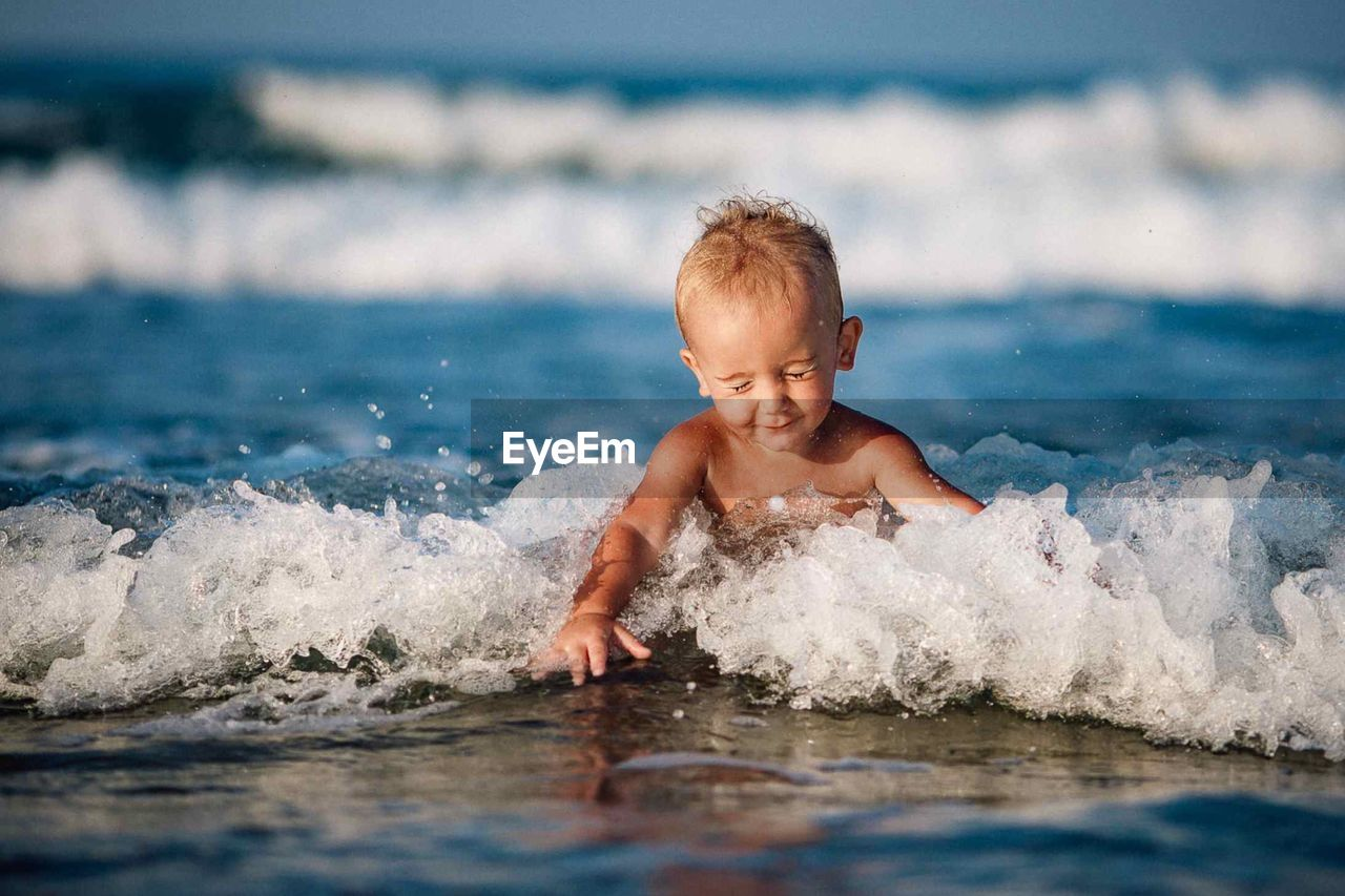 Cute Boy Playing In Waves At Beach