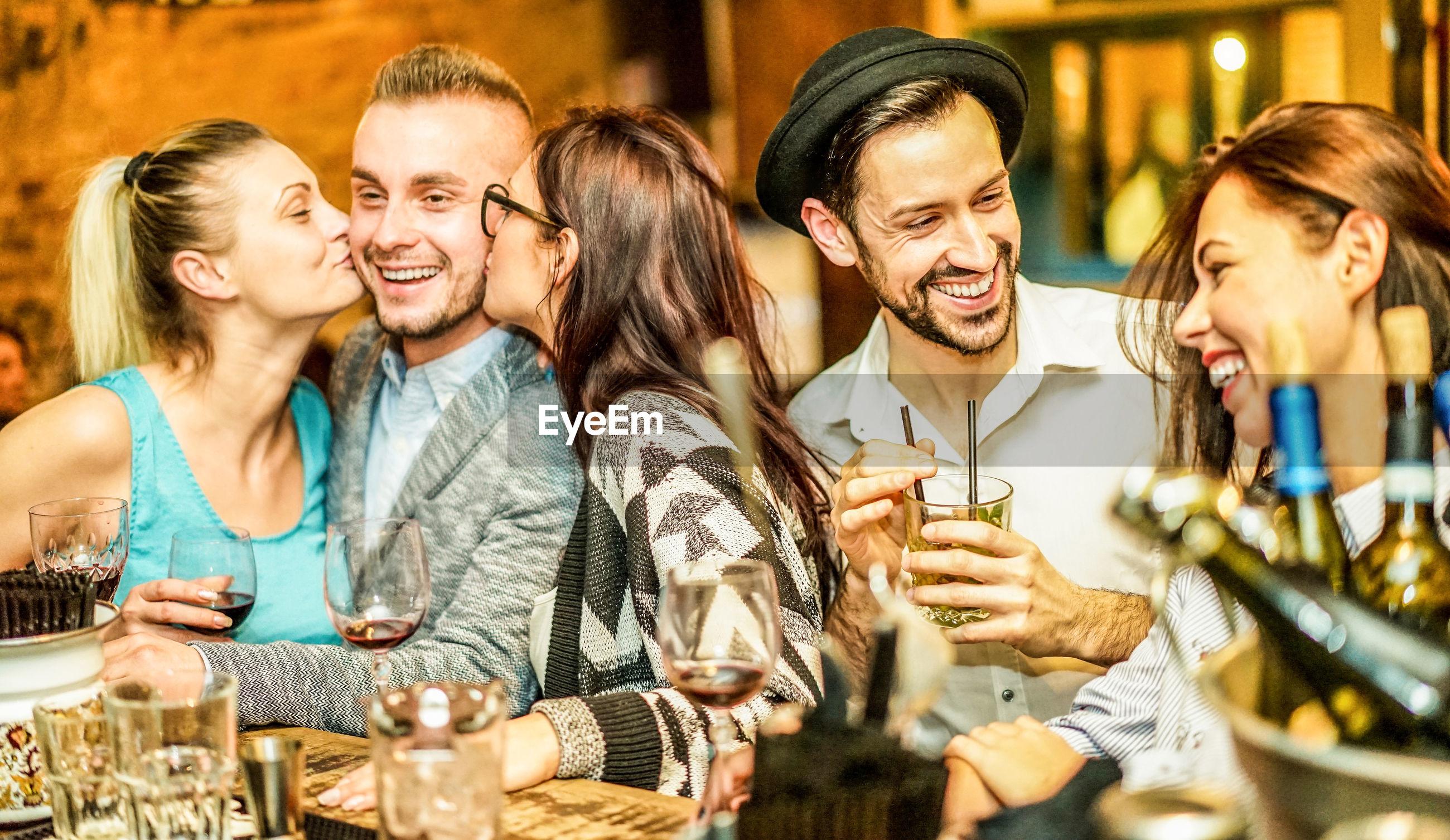 Smiling friends enjoying at restaurant