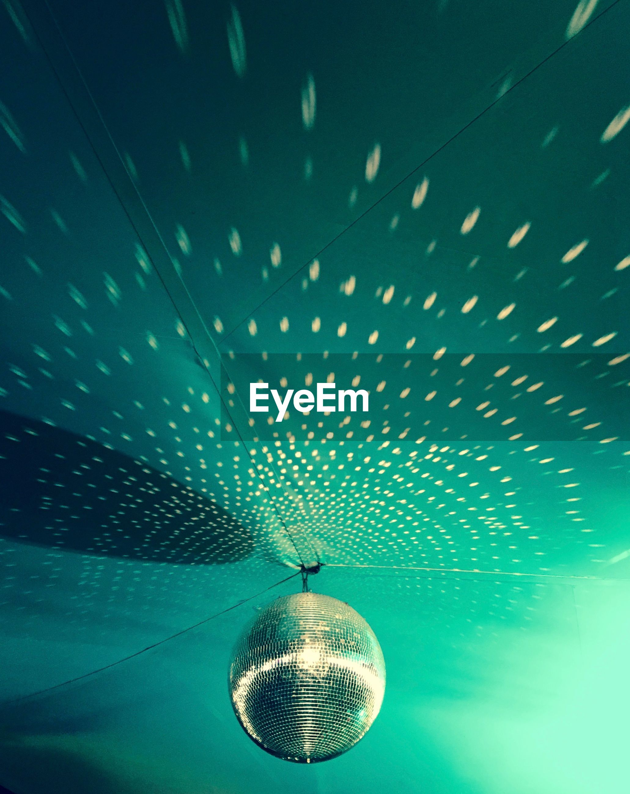 Reflection of lights on ceiling from disco ball at nightclub
