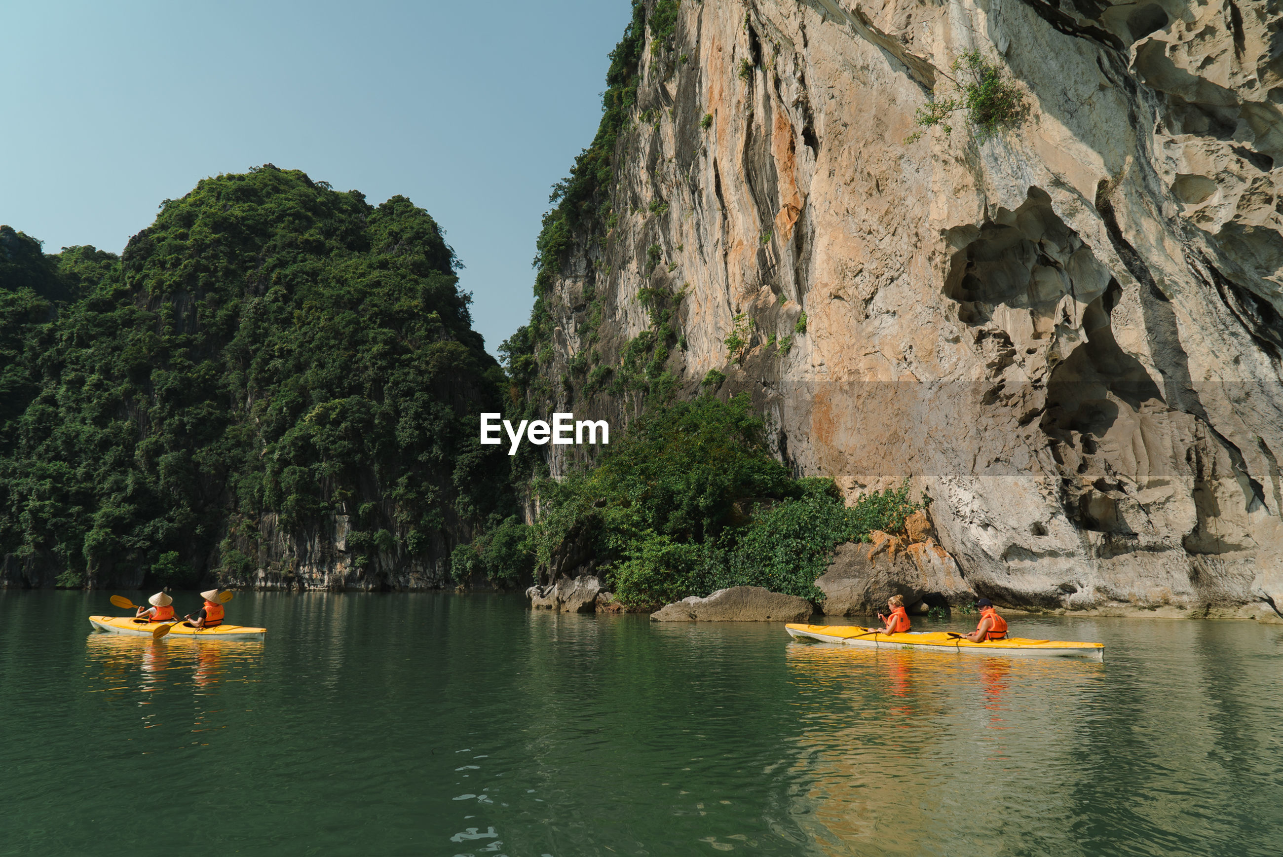People kayaking against rocky cliff
