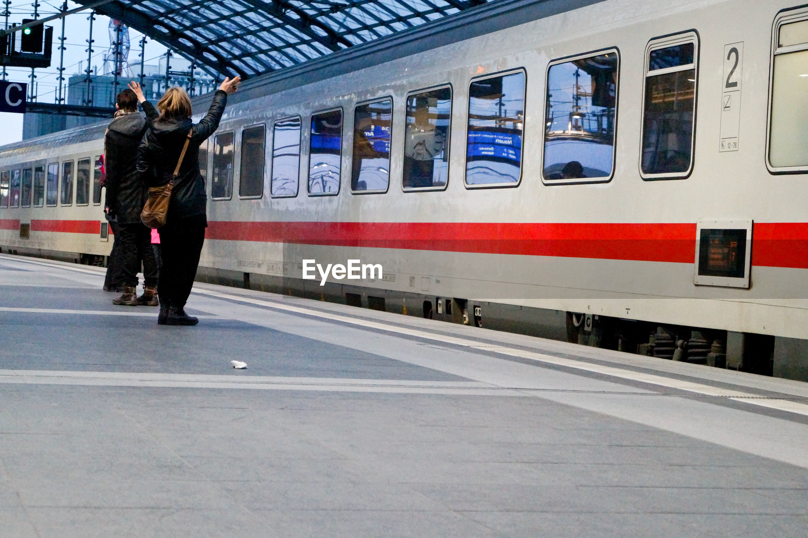Rear view of people waving while standing at railroad station platform