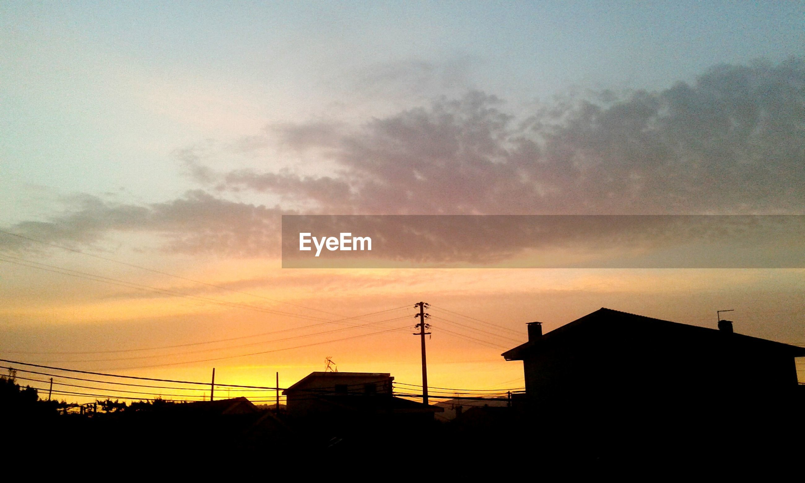 sunset, building exterior, architecture, silhouette, built structure, sky, power line, orange color, electricity pylon, house, low angle view, cloud - sky, residential structure, power supply, connection, cable, electricity, cloud, building, city