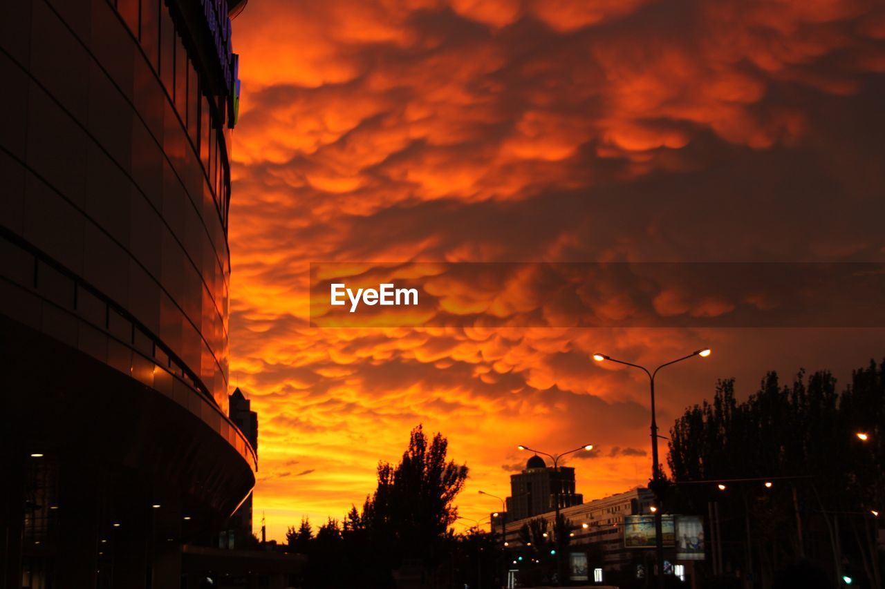 sunset, building exterior, architecture, built structure, sky, city, orange color, dramatic sky, dusk, cloud - sky, no people, outdoors, silhouette, cityscape, tree, nature, illuminated, night, beauty in nature