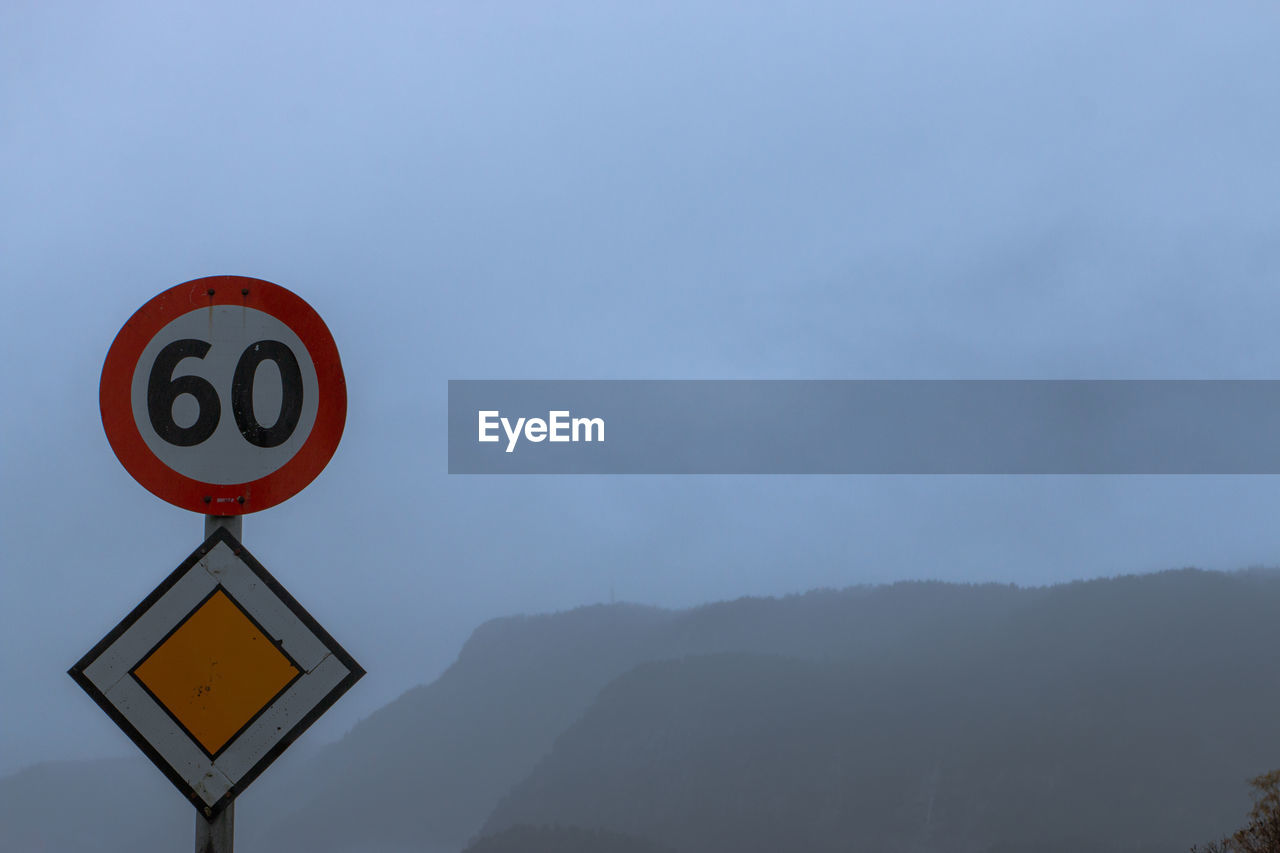 LOW ANGLE VIEW OF ROAD SIGN AGAINST MOUNTAIN