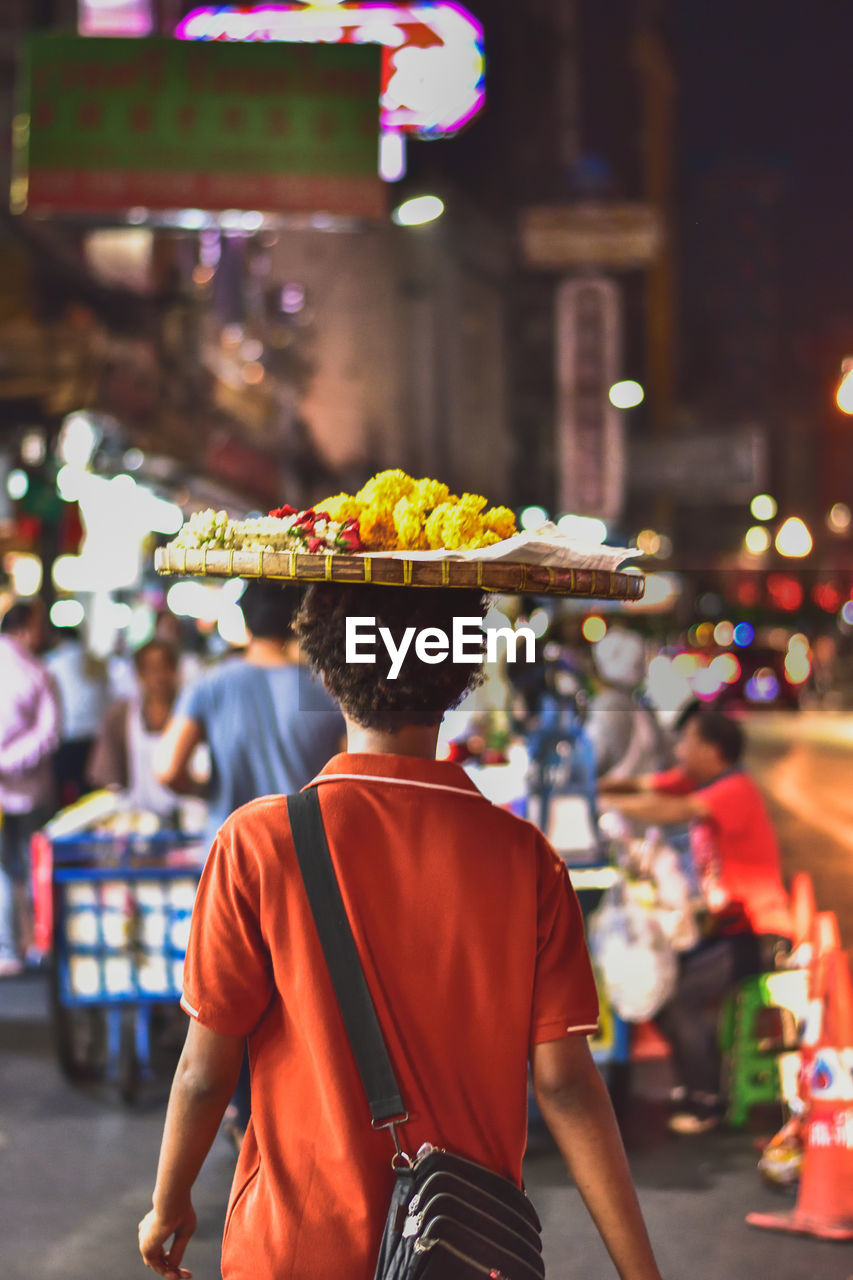 real people, focus on foreground, one person, city, rear view, incidental people, men, clothing, standing, street, hat, retail, market, illuminated, lifestyles, adult, architecture, waist up, night, street market