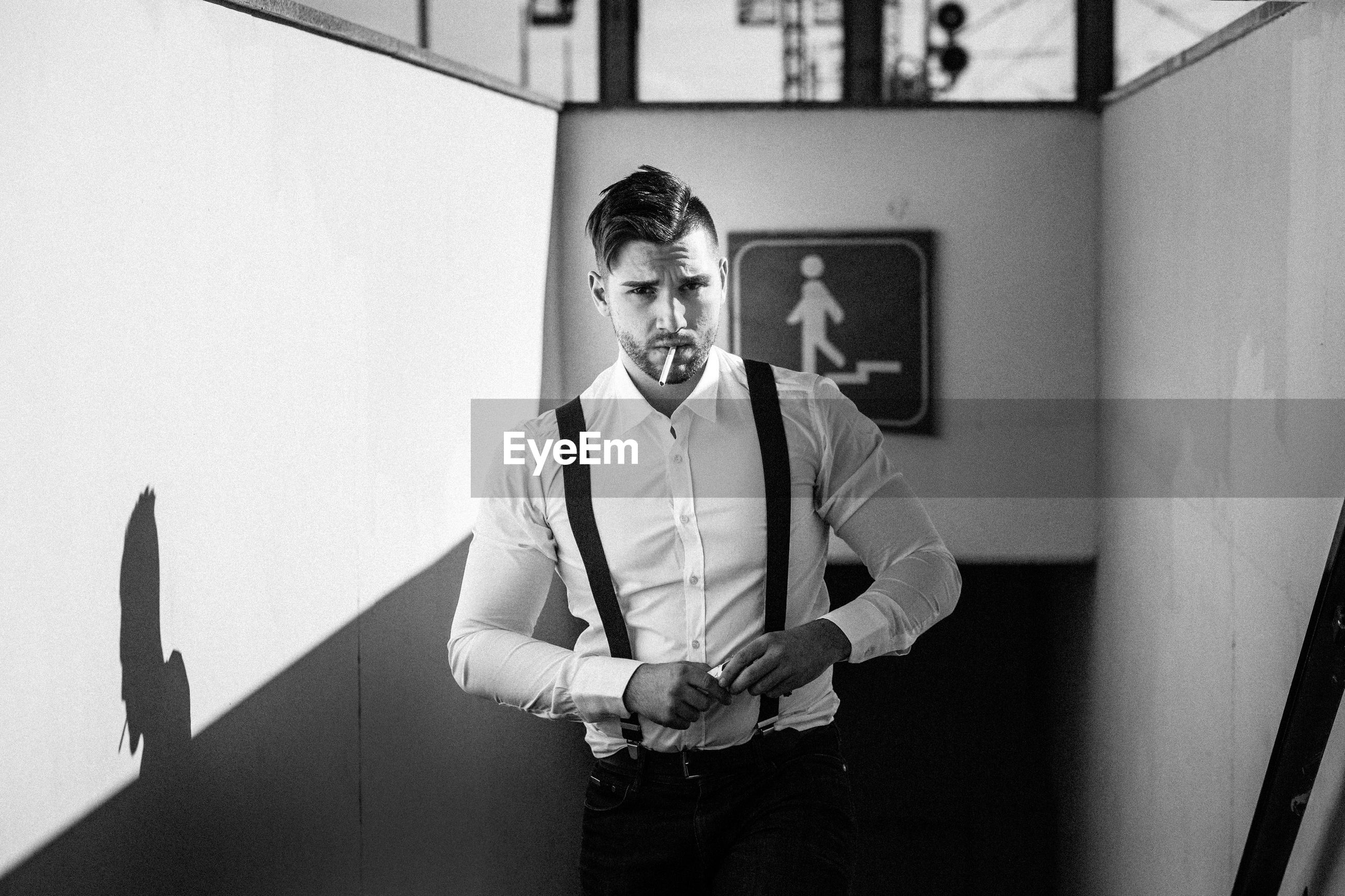 Portrait of handsome man standing on stairs