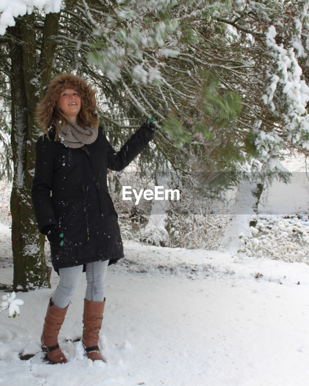 Full Length Of Woman In Warm Clothes While Standing On Snow Covered Field