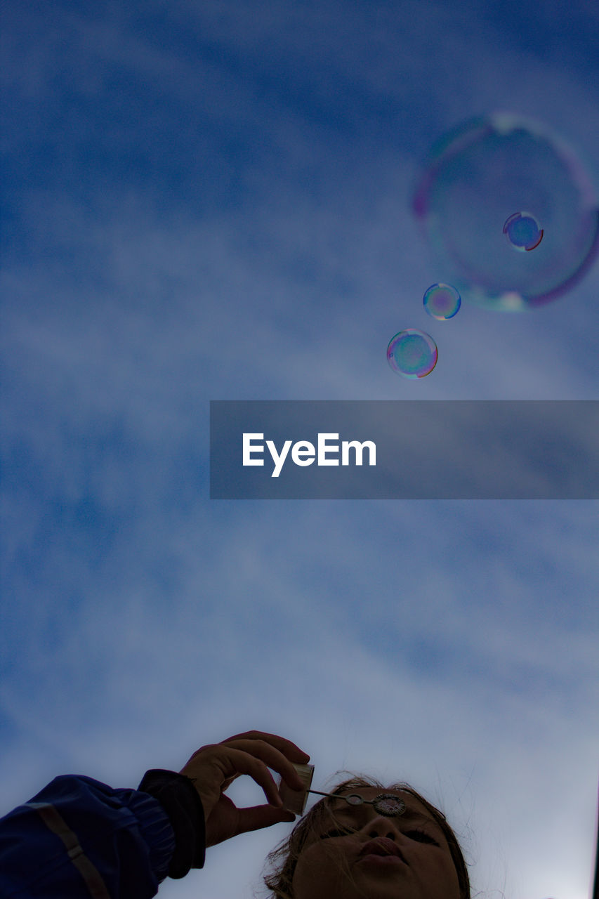 Low angle view of girl blowing bubbles against sky