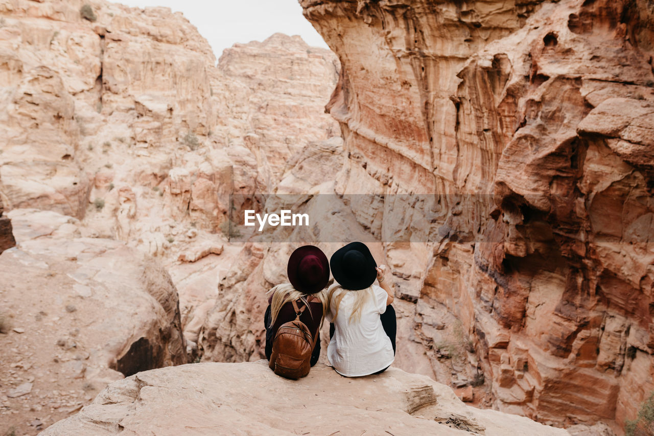 Rear view of friends sitting on rock formation