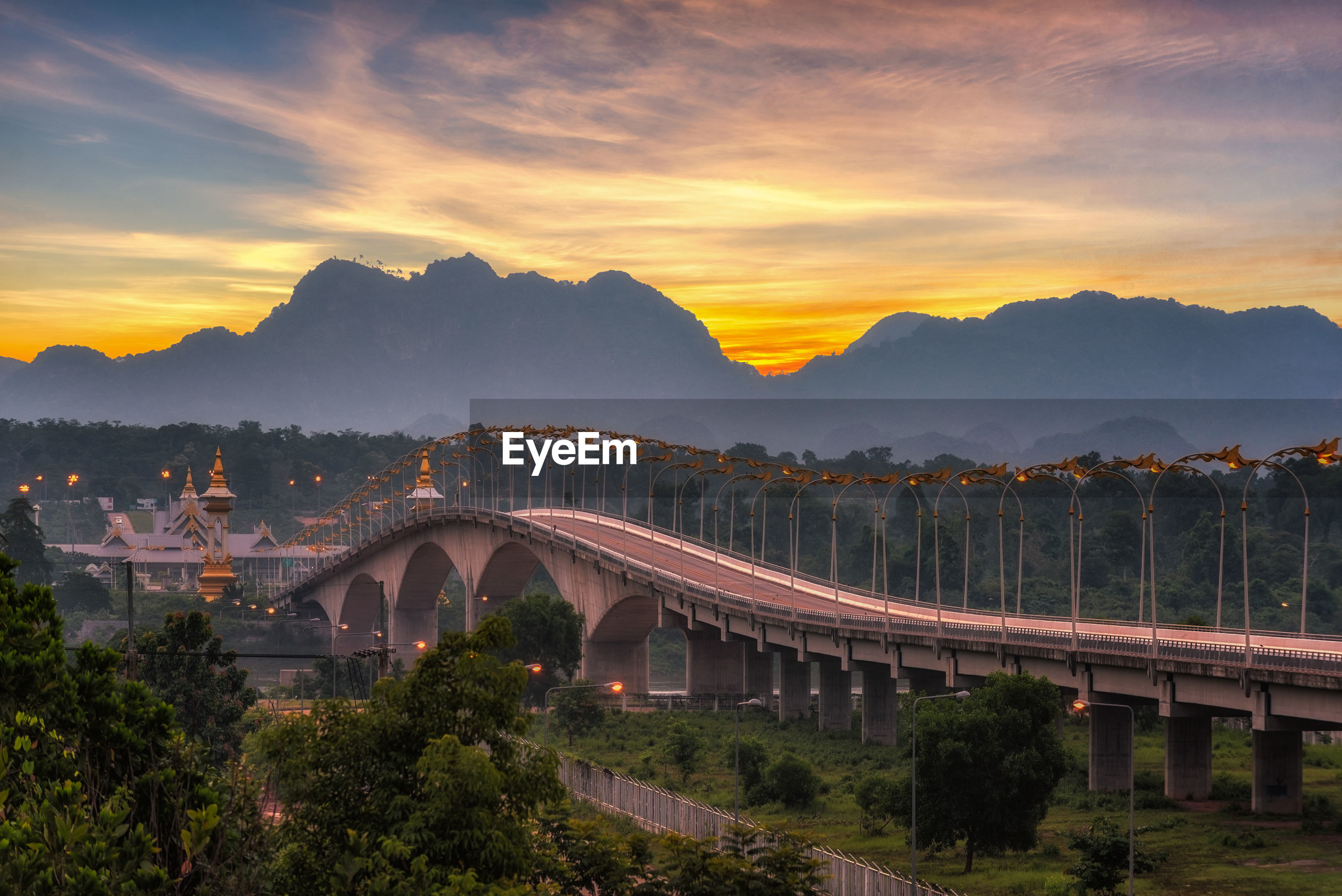 Bridge by mountain against cloudy sky during sunset