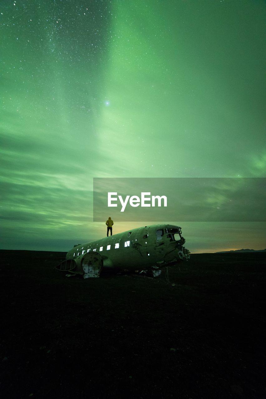 Man Standing On Dc-3 Airplane Against Aurora Borealis At Night