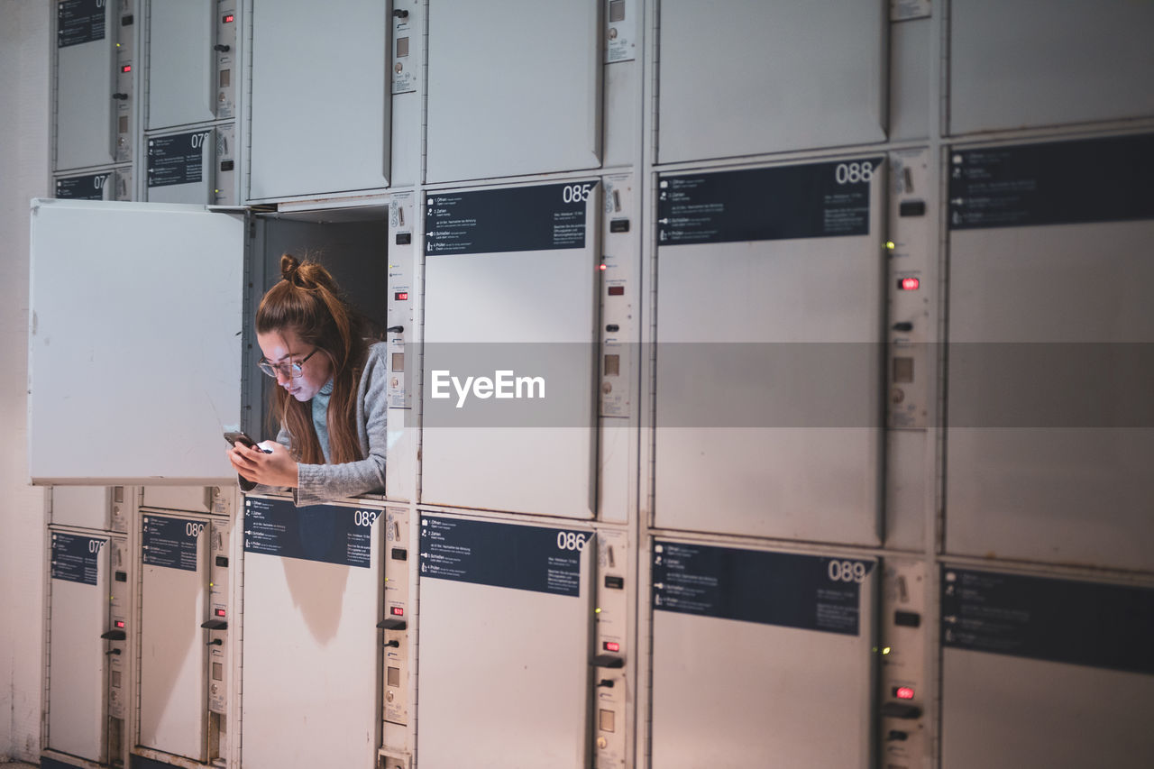 Young Woman Using Phone In Locker