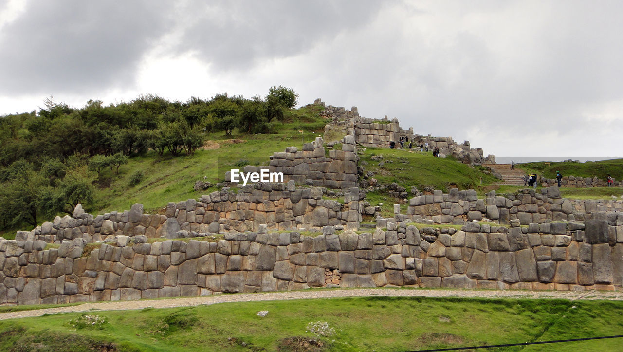history, sky, plant, the past, ancient, cloud - sky, nature, architecture, tree, ancient civilization, grass, built structure, old ruin, green color, travel destinations, wall, day, growth, stone wall, tourism, archaeology, no people, outdoors, ruined