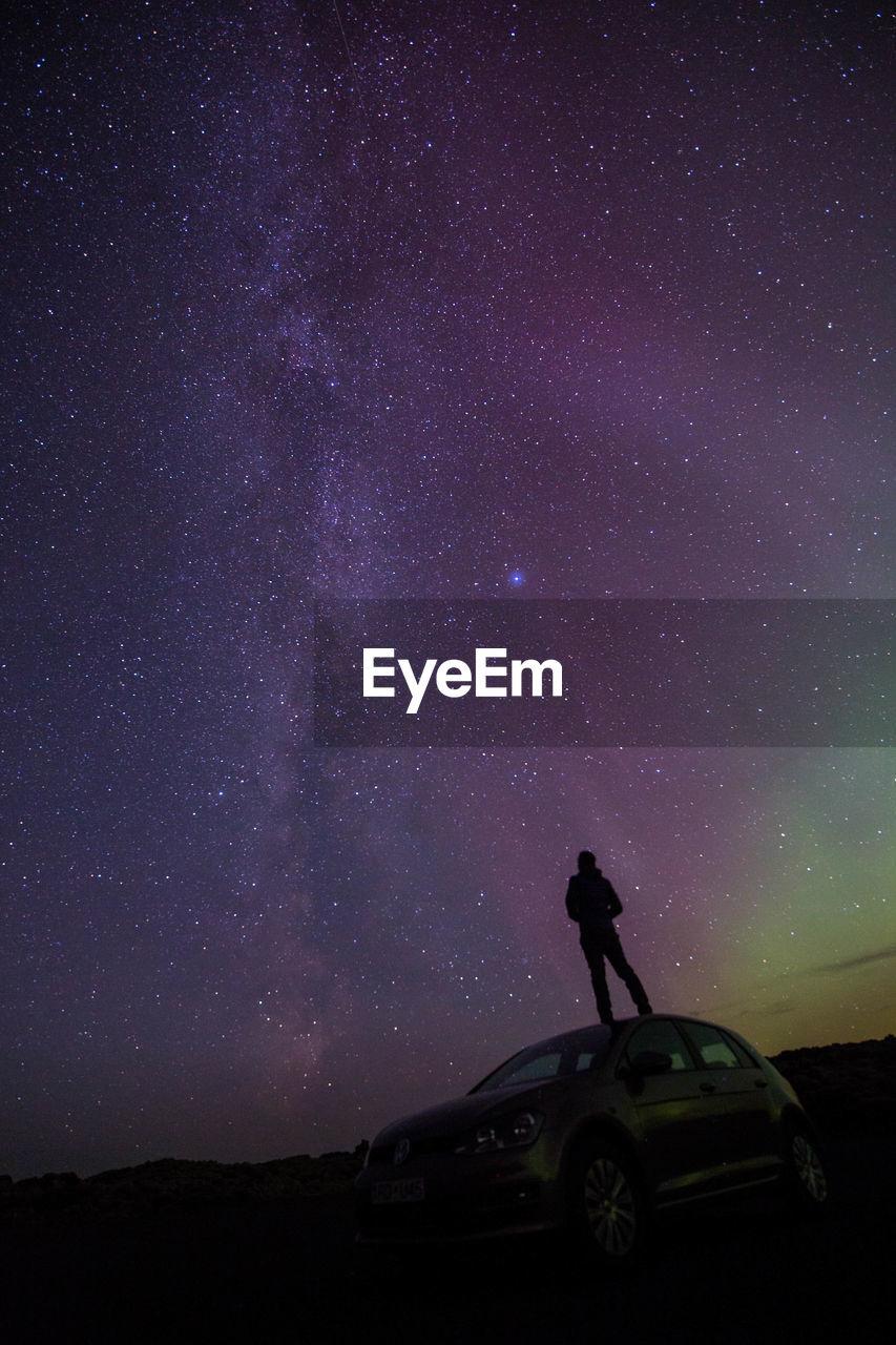 Silhouette Man On Car Looking At Aurora Polaris At Night