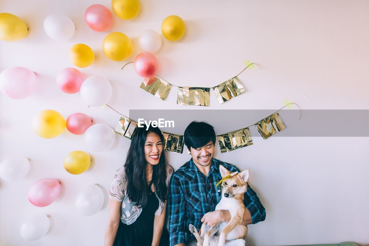 Smiling couple with dog against decorated wall