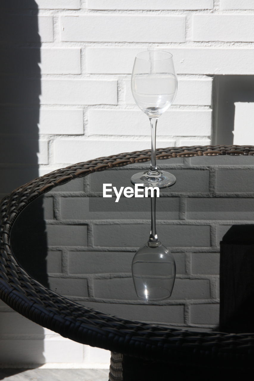 Wineglass on table against wall