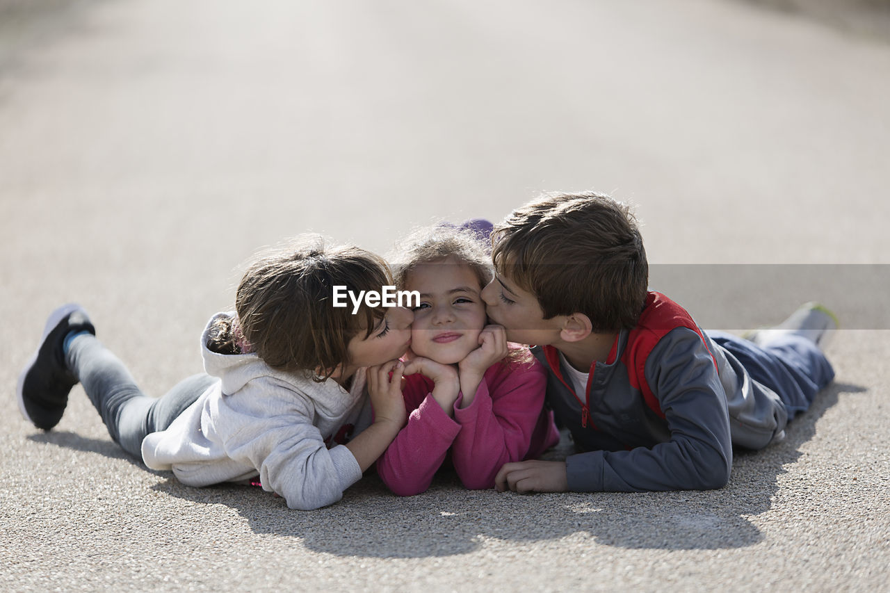 Siblings Kissing Sister While Lying Down On Road