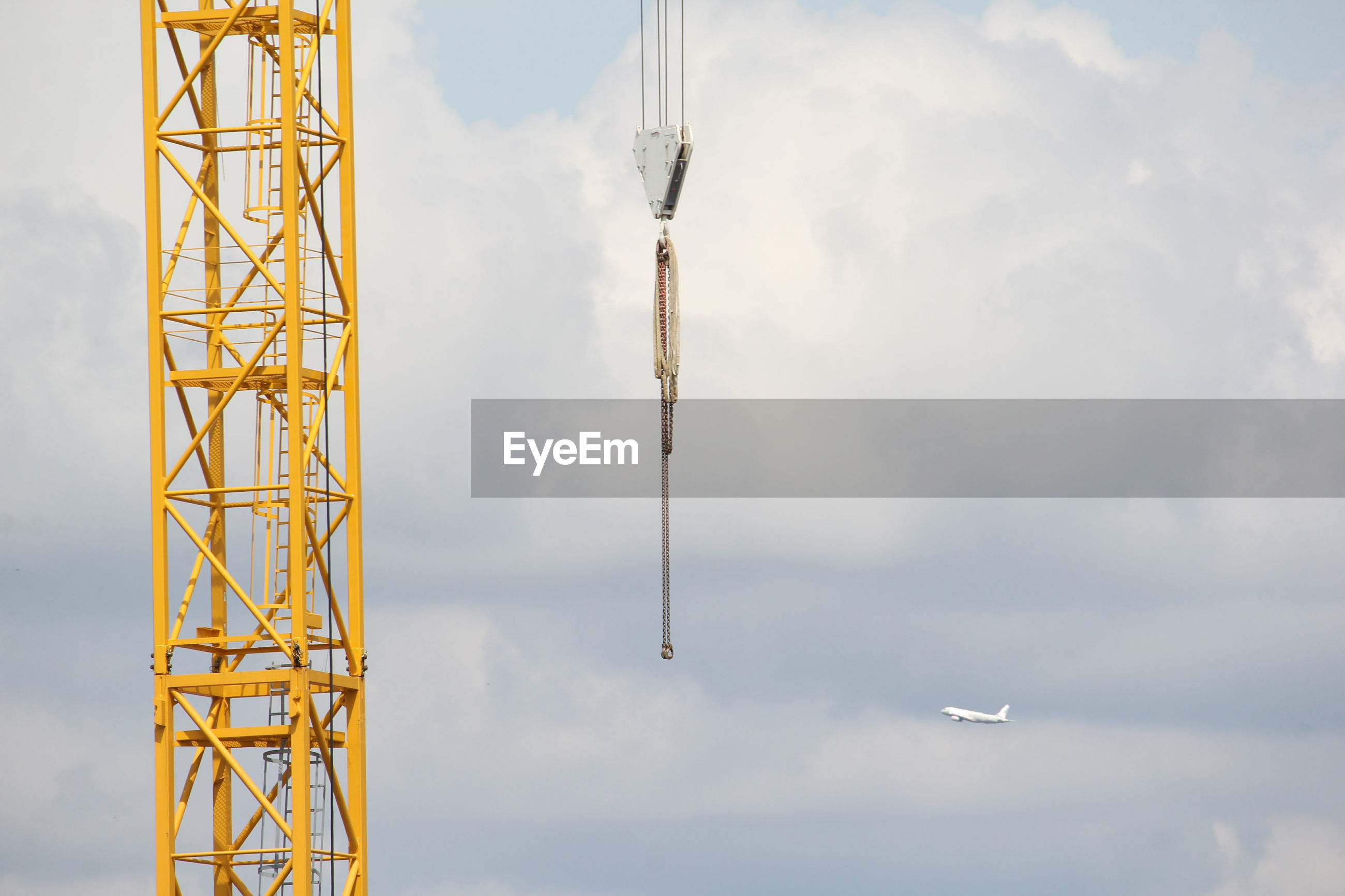 Low angle view of crane against sky with plane flying through chain