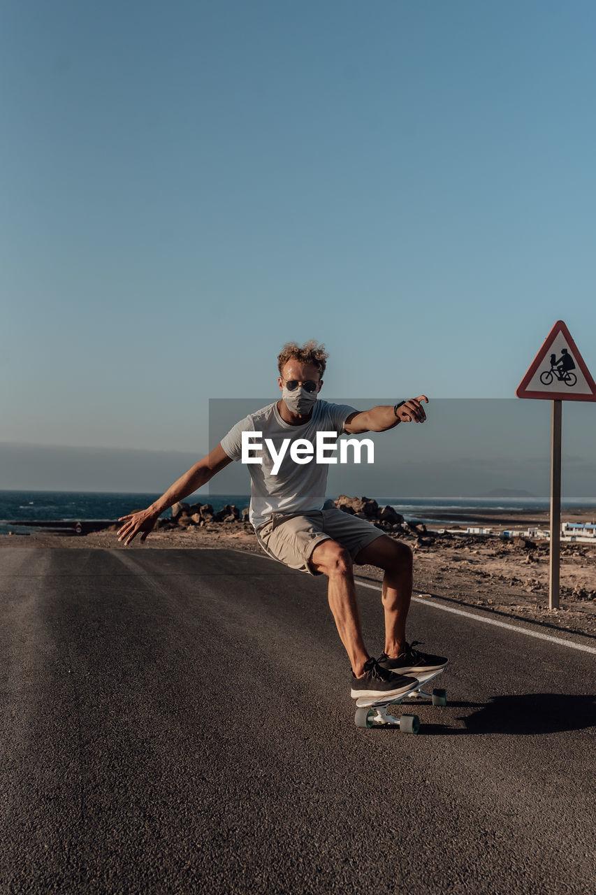 Full length of man on electric skateboard  against clear sky