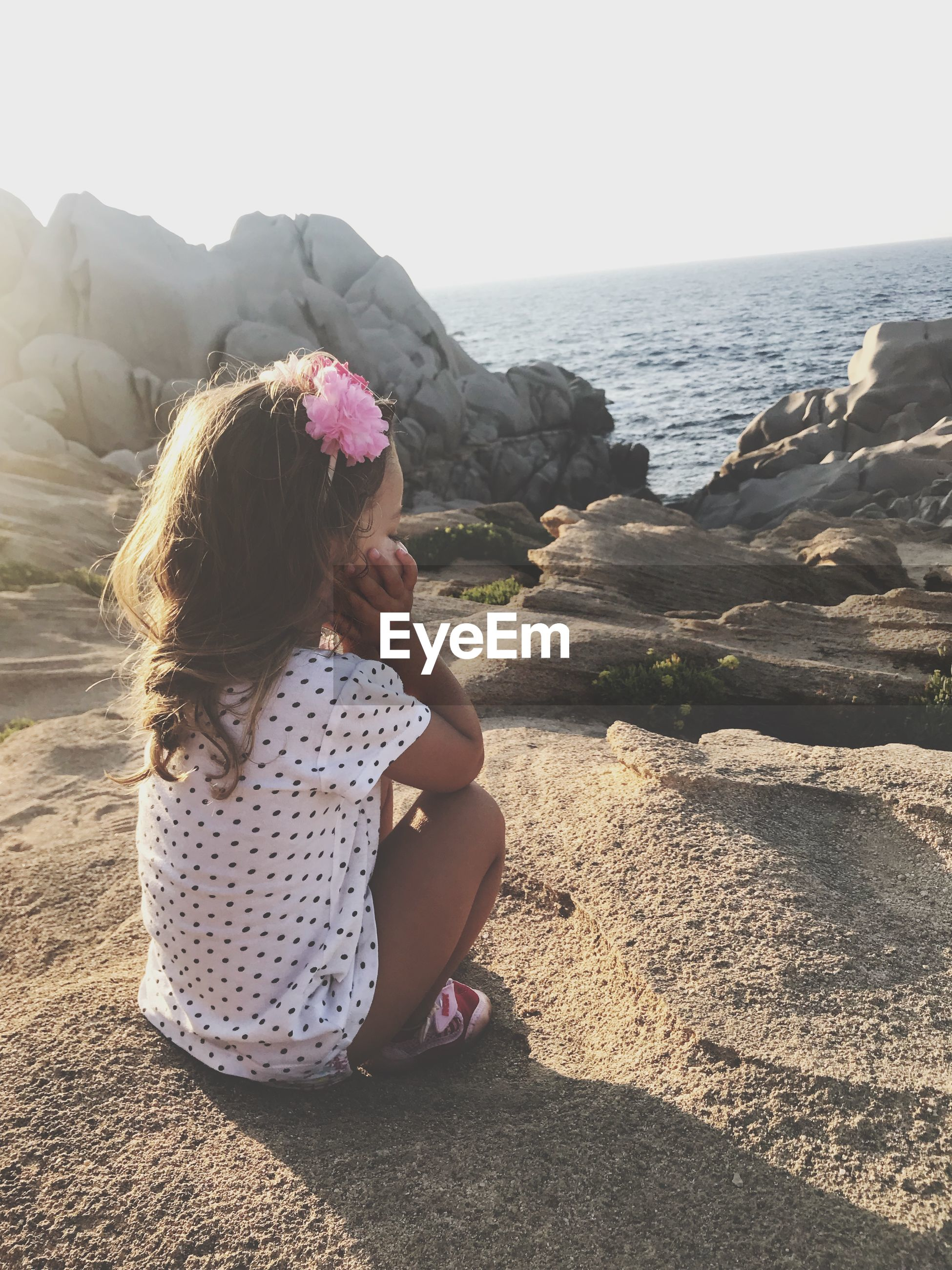 Full length of girl on rock by sea against sky