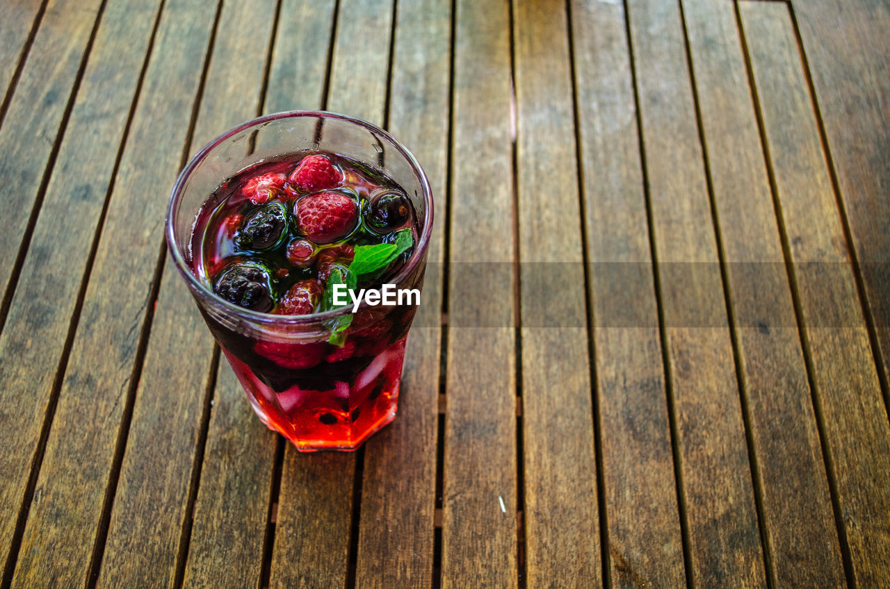Directly above shot of glass with raspberry on wooden table