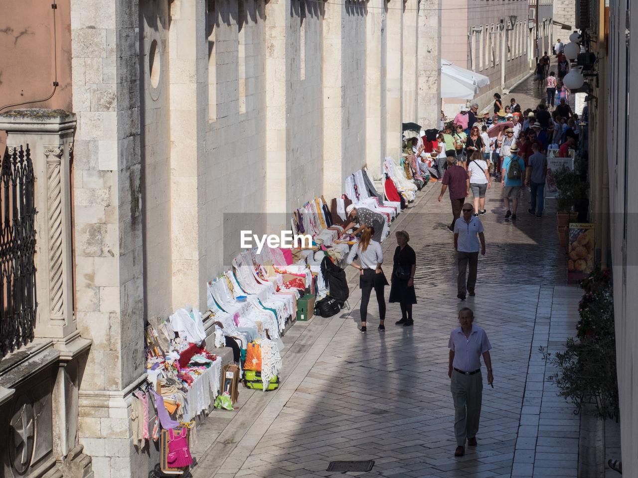 GROUP OF PEOPLE WALKING ON NARROW STREET