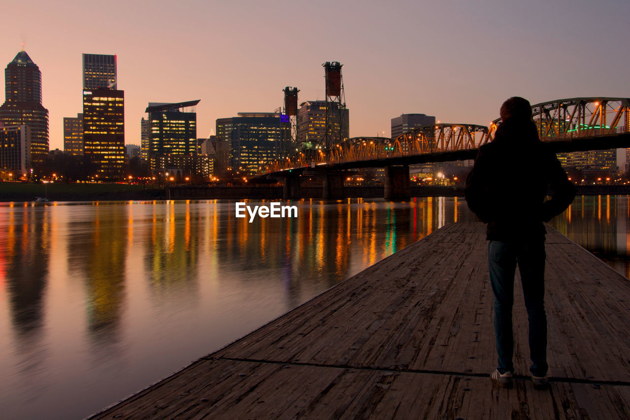 Rear View Of Man Standing On Jetty In River Against Illuminated City